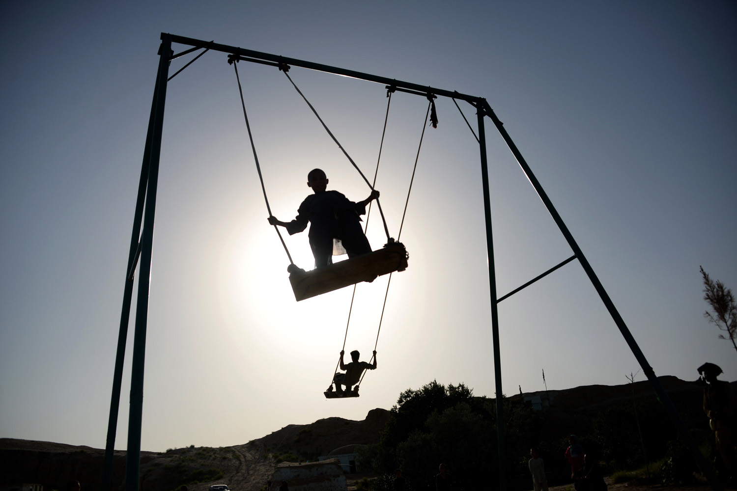 Afghan youth play on swings on the outskirts of Mazar-i-sharif on May 13, 2014.