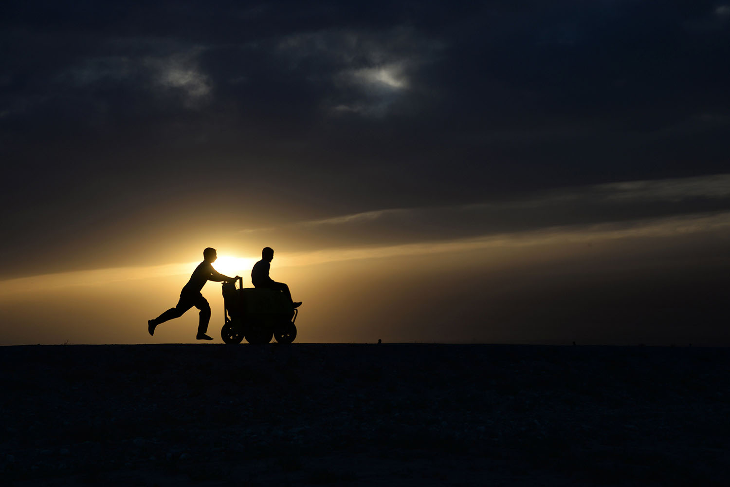 An Afghan youth pushes a friend on a ice-cream cart as the sun sets on the outskirts of Mazar Sharif on May 16, 2014.