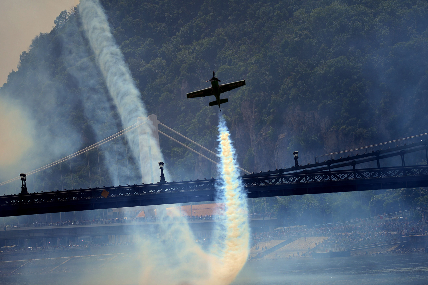 Hungarian pilot and European champion Zoltan Veres flies under the oldest Hungarian bridge, the 'Lanchid' (Chain Bridge) with his 'MXS' type plane on May 1, 2014 during a Red Bull flying and car show around the Danube River of Budapest downtown.