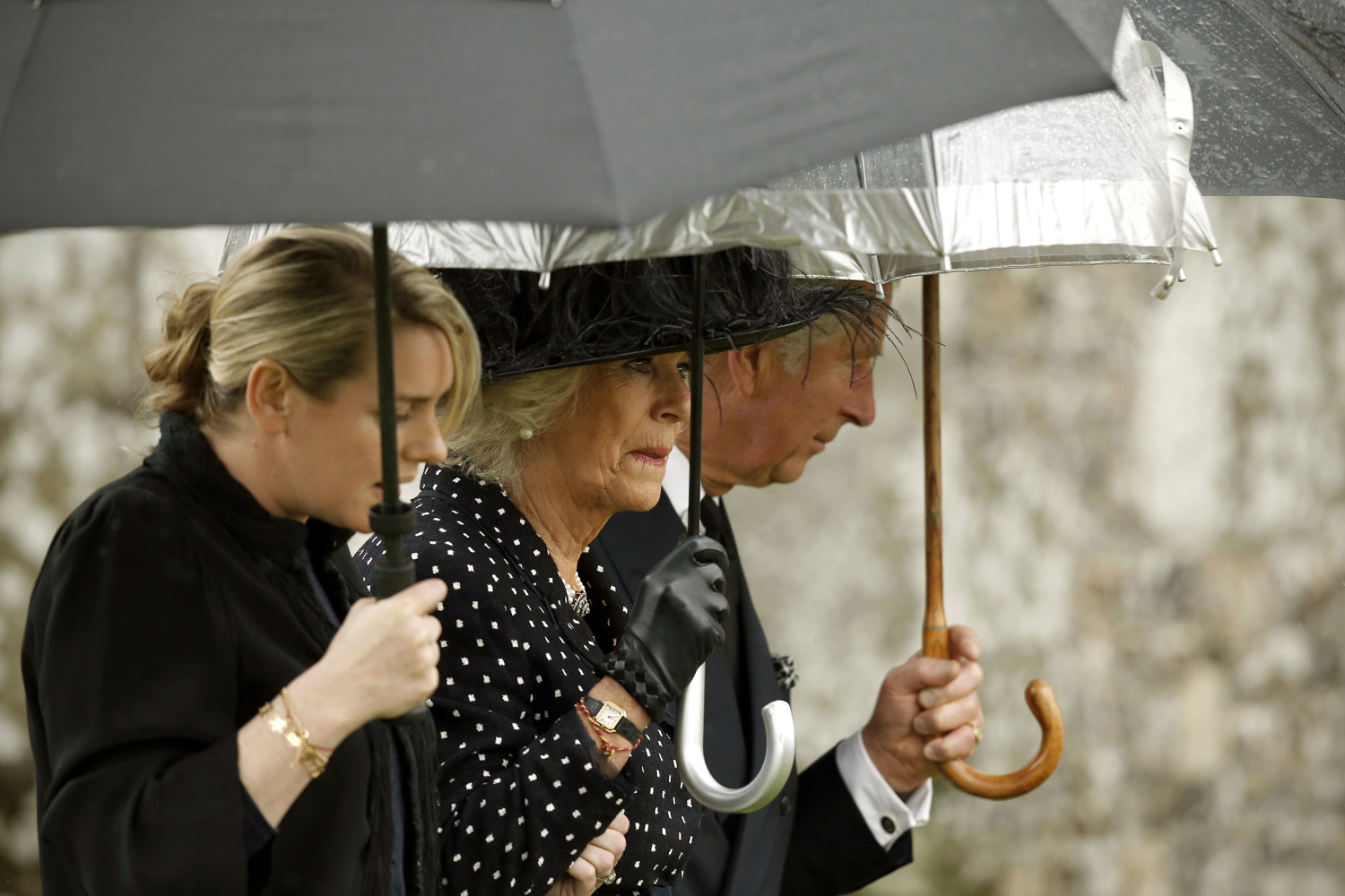 May 1, 2014. Britain's Prince Charles, Prince of Wales (R) arrives with his wife Camilla, the Duchess of Cornwall (C), and her daughter Laura Lopes for the the funeral of her brother, Mark Shand, at Holy Trinity Church in Stourpaine, Dorset, England.