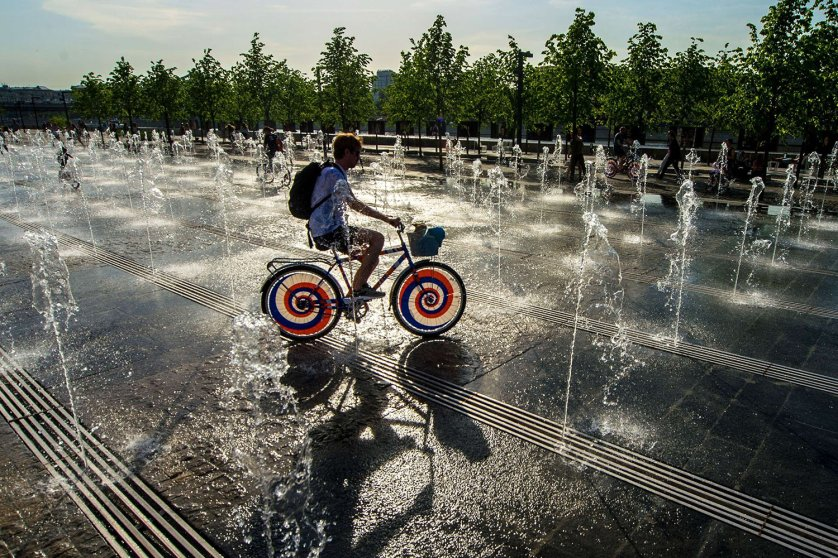 A teenager rides a bike across fountains in central Moscow, on May 19, 2014.