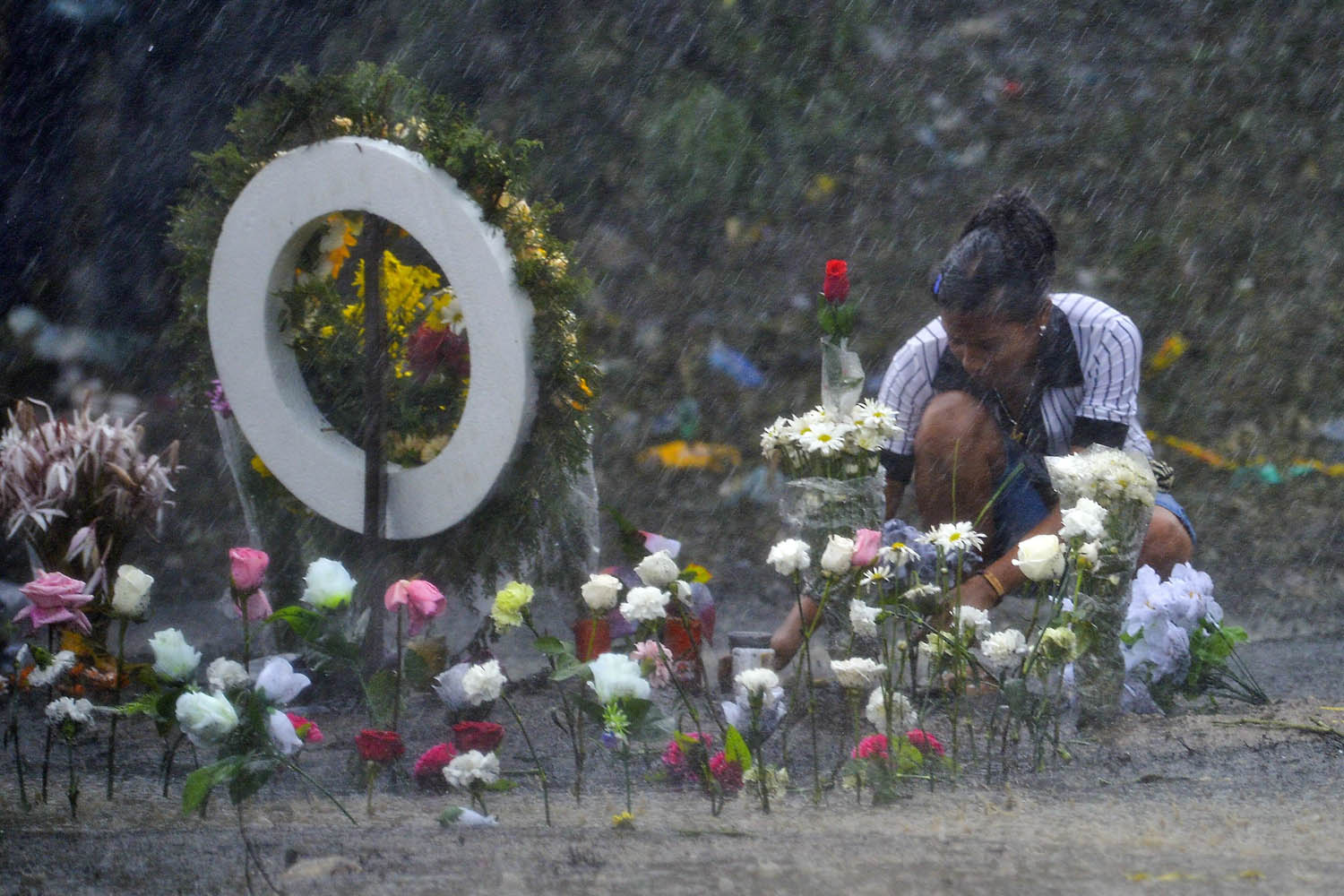 May 19, 2014.                                A relative lays flowers in honor of the 32 chlidren burnt to death inside a school bus in Fundacion, department of Magdalena, Colombia.