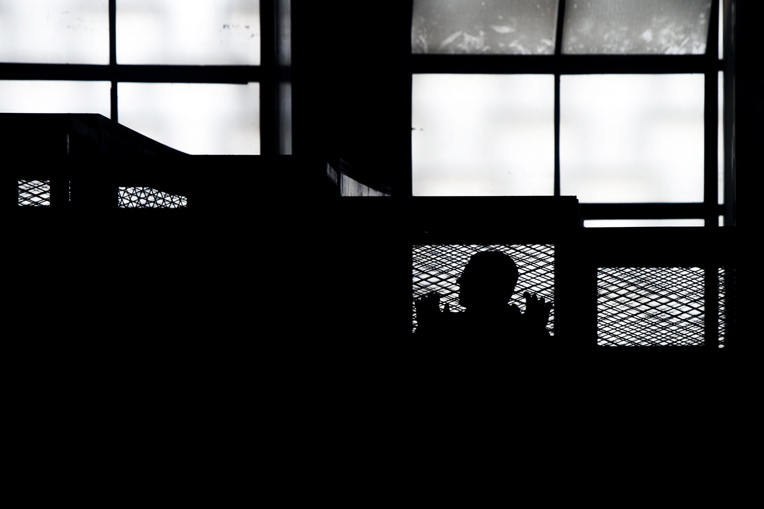 May 22, 2014. An Al-Jazeera channel's journalist stands inside the defendants cage with his colleagues during their trial for allegedly supporting the Muslim Brotherhood at Cairo's Tora prison, Egypt.