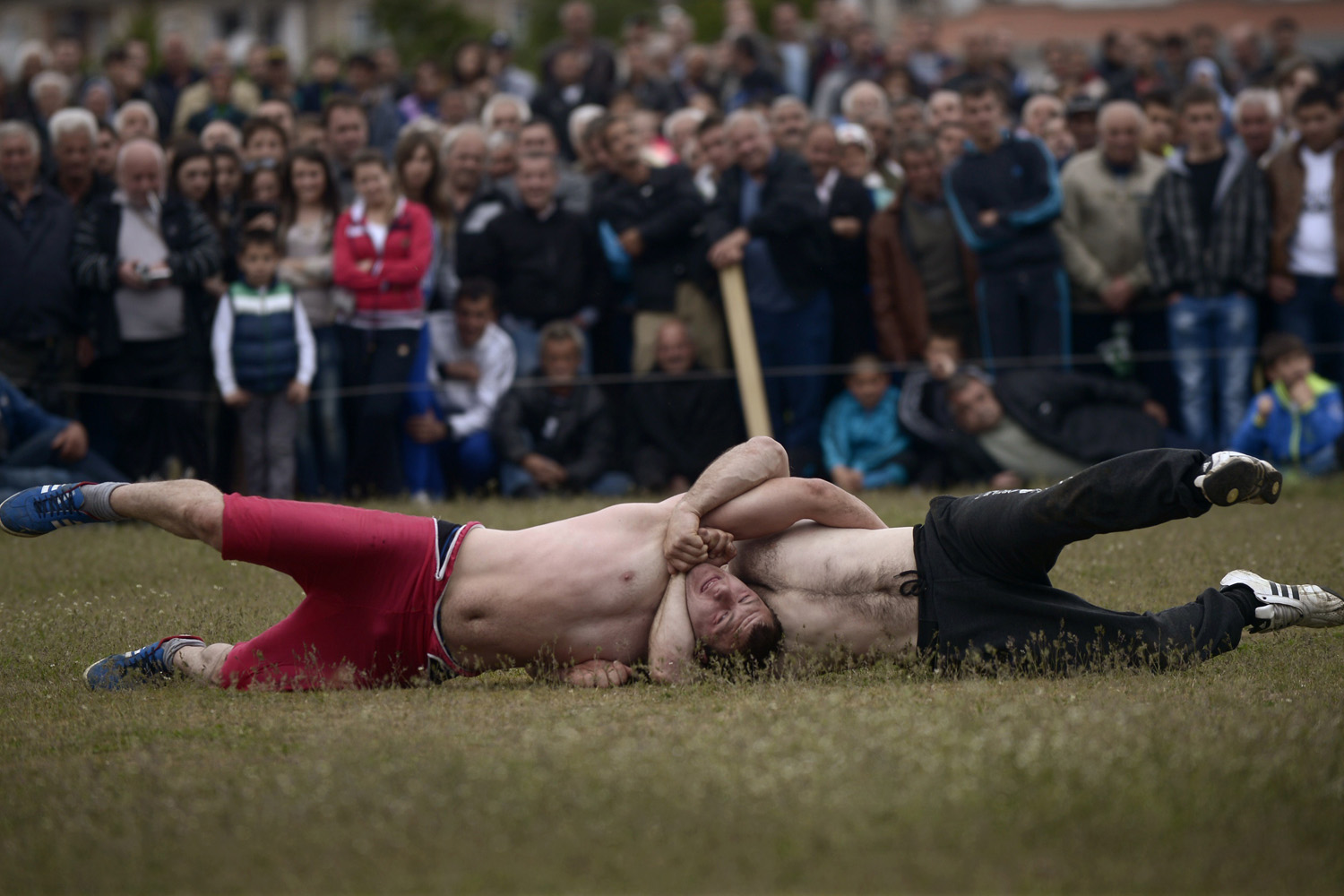 May 4, 2014. Competitors are locked into a strangulation during a traditional wrestling tournament, part of a holiday marking the circumcisions of young boys in the village of Draginovo.