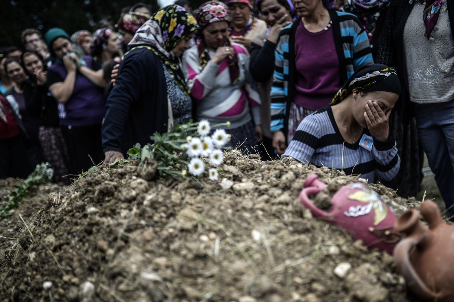 May 15, 2014. Duygu Colak, holds soil from her husband Ugur's grave during a funeral ceremony in the western town of Soma in the Manisa province.