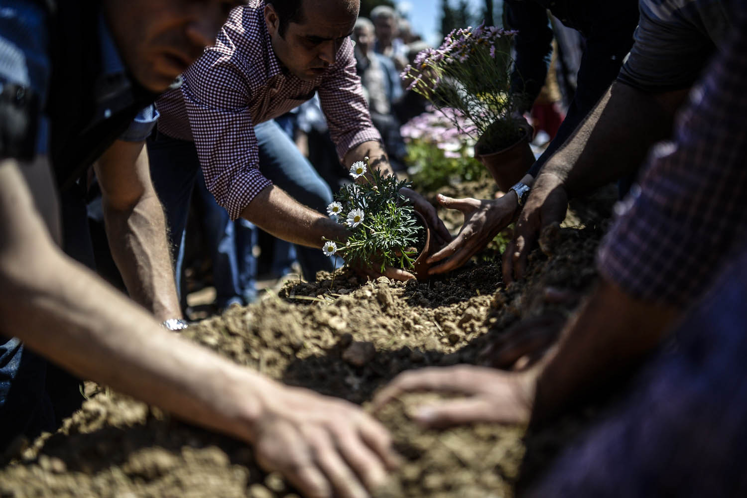 May 18, 2014.                               People mourn their relatives at the cemetery where some of the 301 people killed after an explosion and fire in a coal mine were buried, at Soma in Manisa,  Turkey.