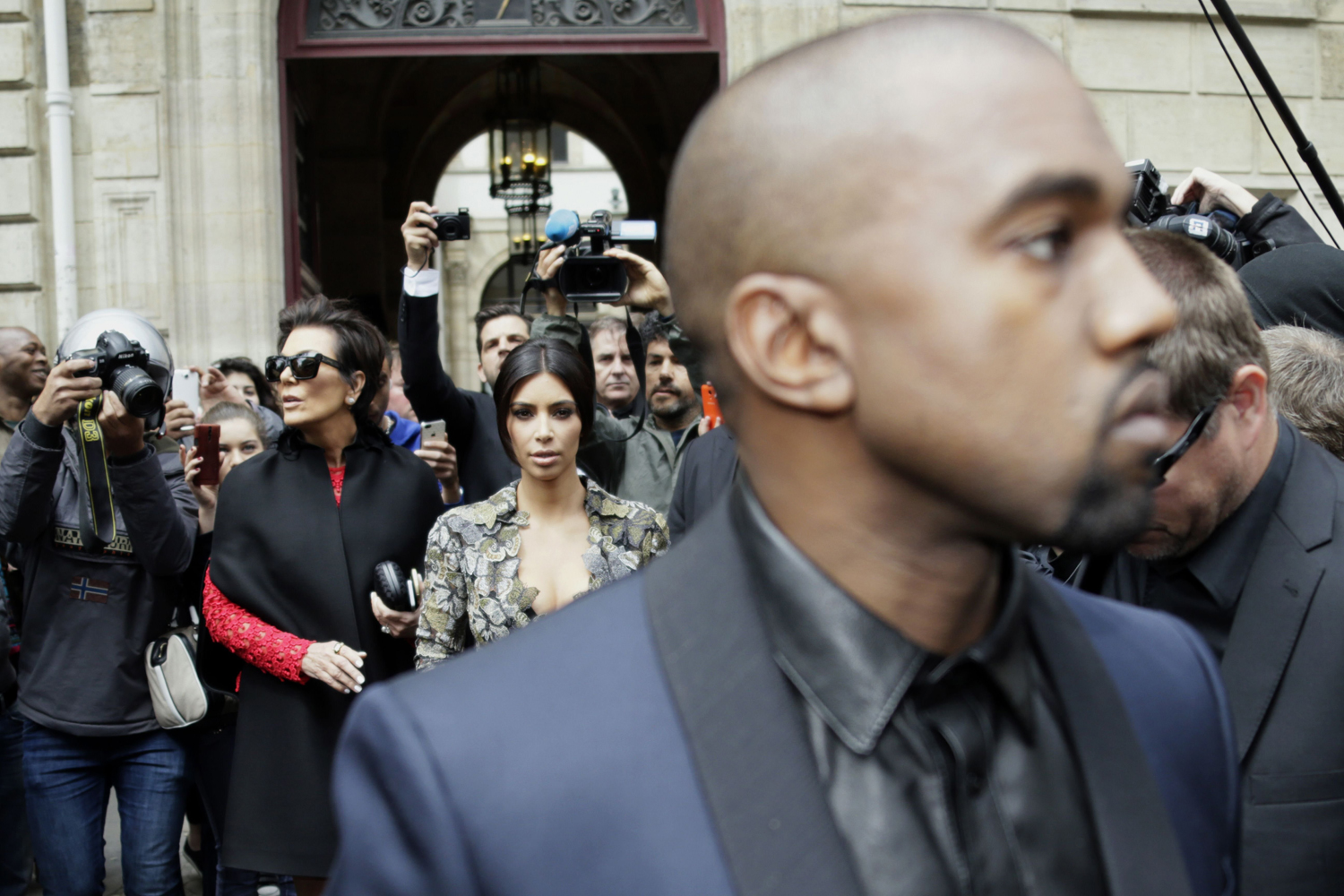 May 23, 2014. Kim Kardashian (C) pushes a stroller next to her partner Kanye West (R) and her mother Kris Jenner (2L) as they leave their hotel in Paris.