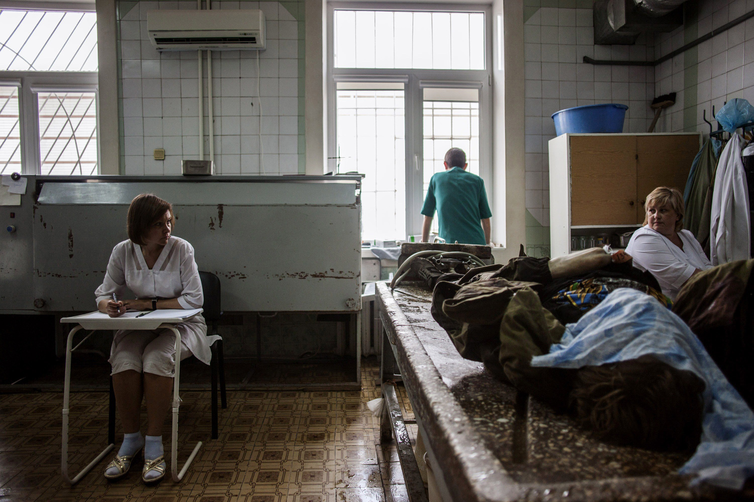 May 27, 2014. Ukrainian medical staff prepare to clean the body of a killed pro-Russian fighter at the Kalinina morgue in the eastern Ukrainian city of Donetsk.