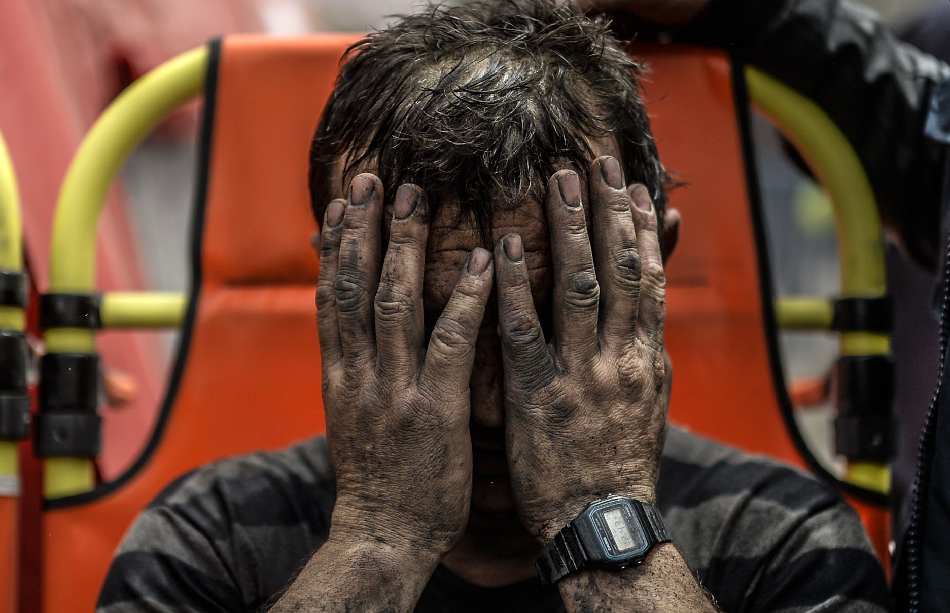 A miner reacts after being affected with toxic gas while searching for co-workers who remain trapped underground on May 14, 2014 after an explosion and fire in their coal mine in the western Turkish province of Manisa.