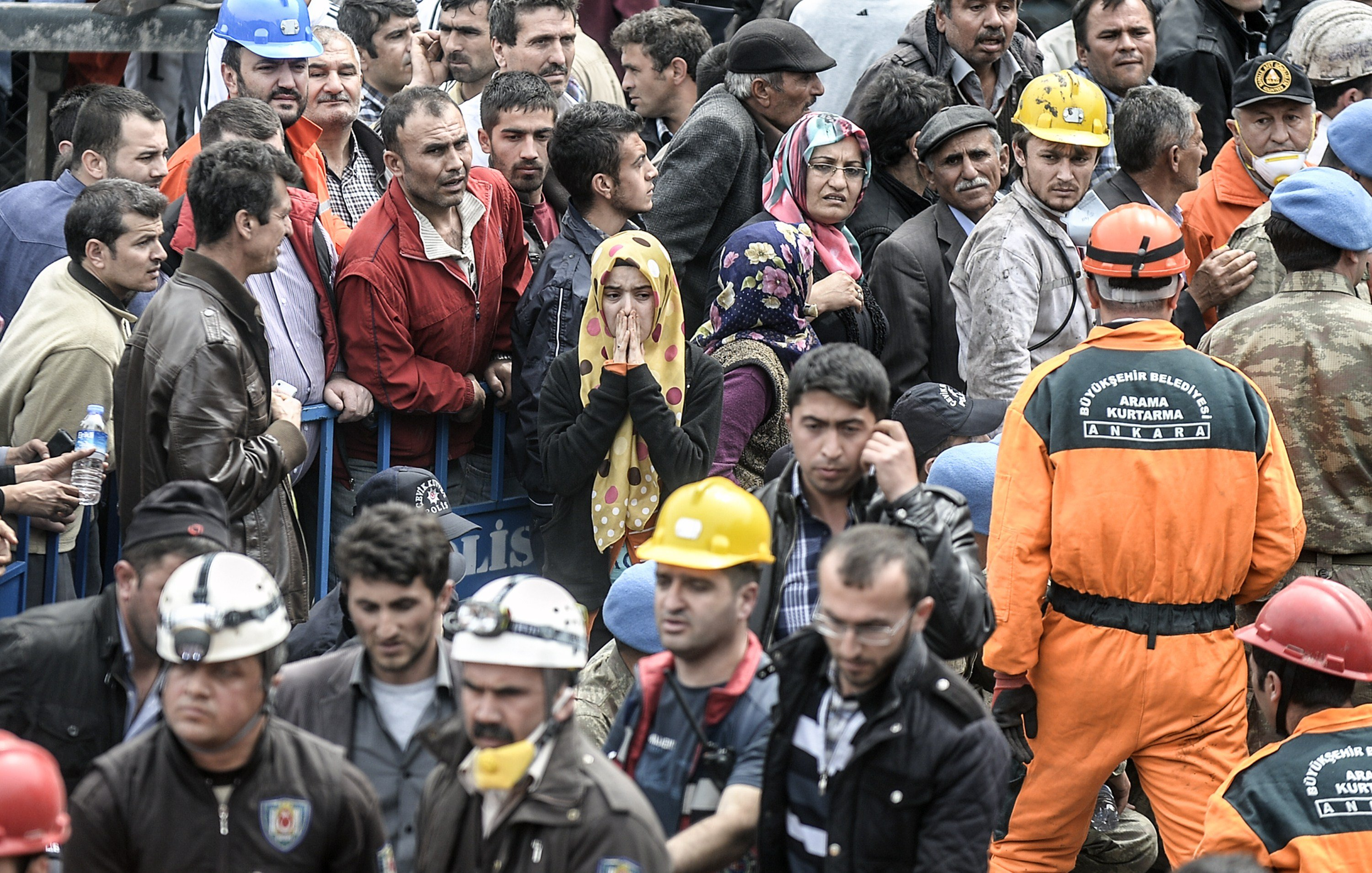 People gather, searching for their relatives, as rescuers carry out bodies of dead miners on May 14, 2014 after an explosion and fire in a coal mine in the western Turkish province of Manisa.