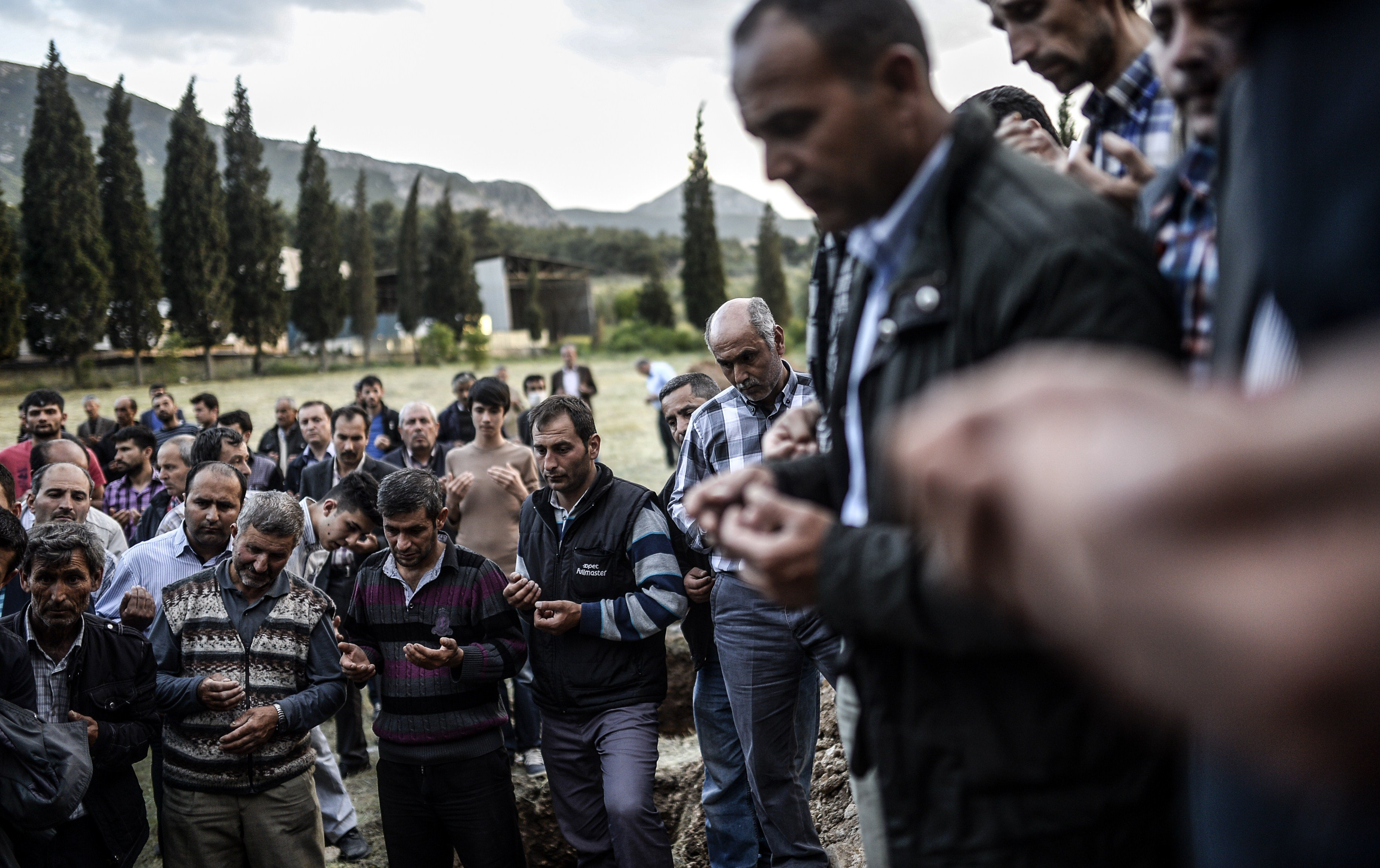 Turkish people mourn in a cemetary in Manisa on May 14, 2014, during the funeral of miners killed in a mine blast the day before in the western Turkish province of Manisa.
