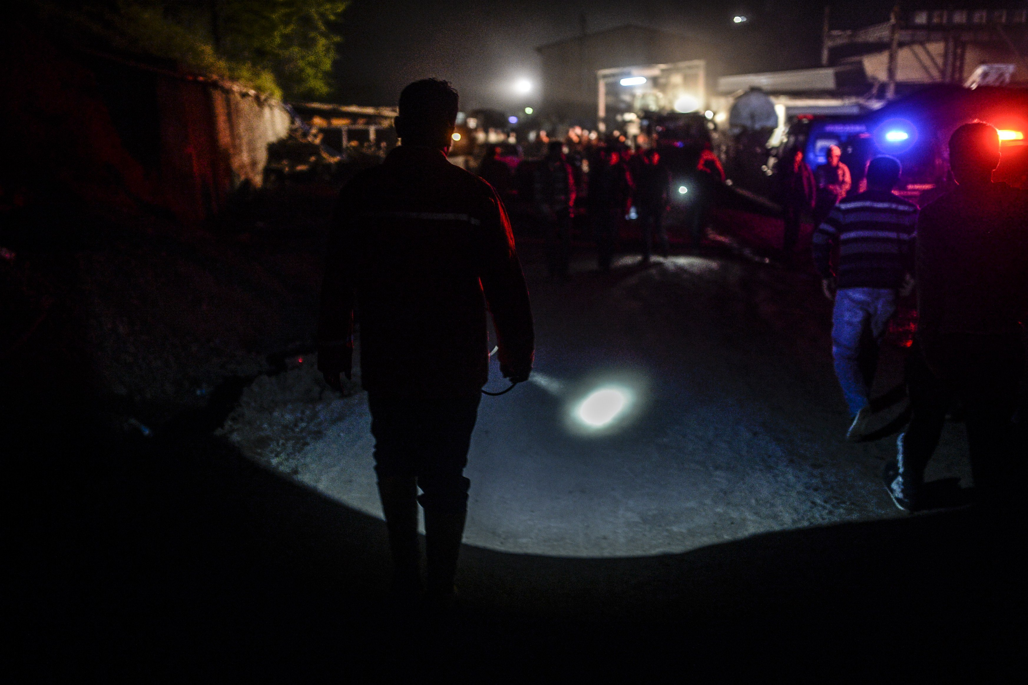 A miner use his lighter as miners wait at the gate of a mine after an explosion in Manisa on May 13, 2014.
