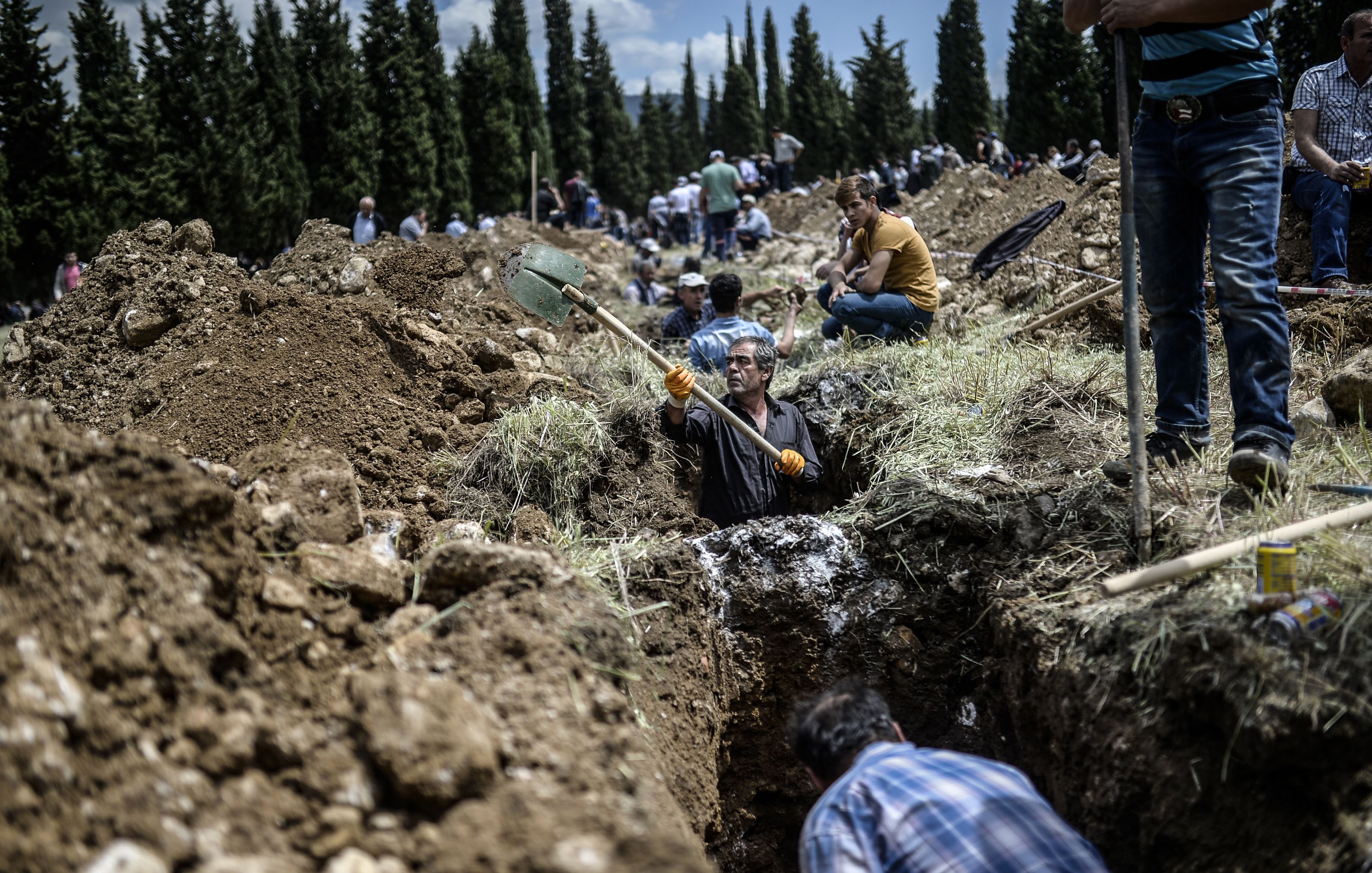 People dig graves for miners in a cemetery during the funeral ceremony of miners who died in an explosion on May 15, 2014, in the western town of Soma in the Manisa province.
