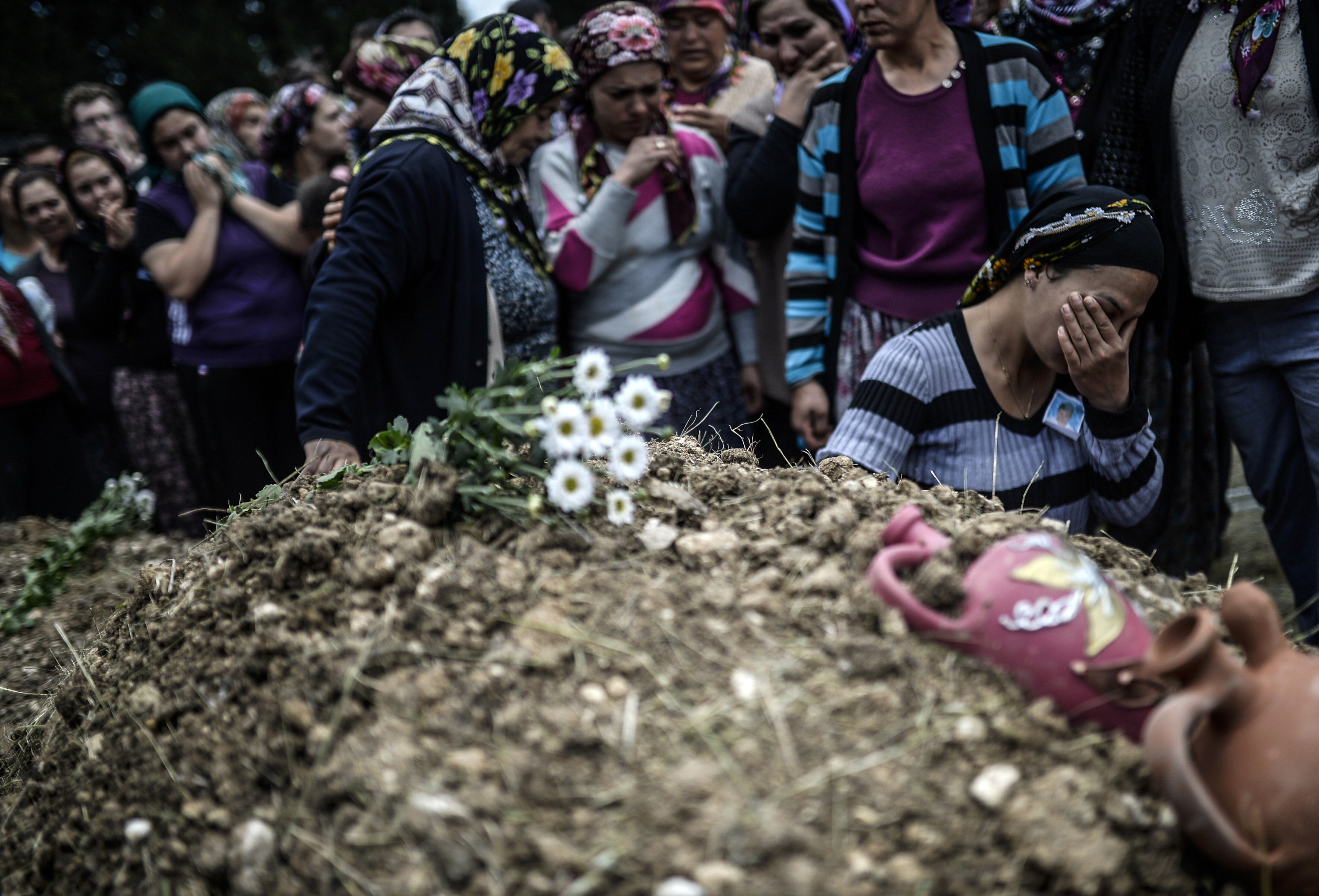 Duygu Colak, reacts as she sits in front of her husband Ugur's grave during a funeral ceremony in the western town of Soma in the Manisa province on May 15, 2014.