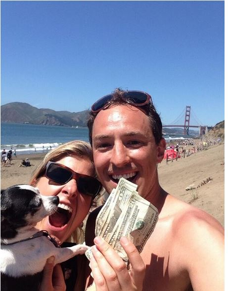 Forrest Hanson holds up the $100 in cash he found on San Francisco's Baker Beach over Memorial Day Weekend in an online scavenger hunt.