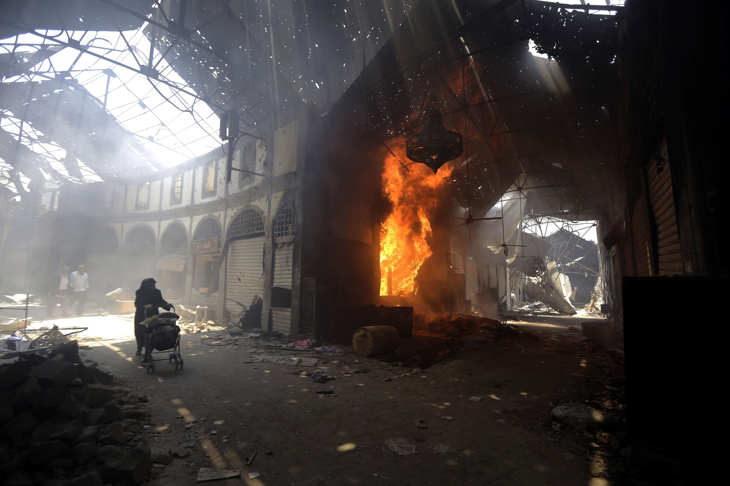 May 12, 2014. A woman walks past a burning shop in the Maskuf market in the Old City of Homs, north of Damascus.