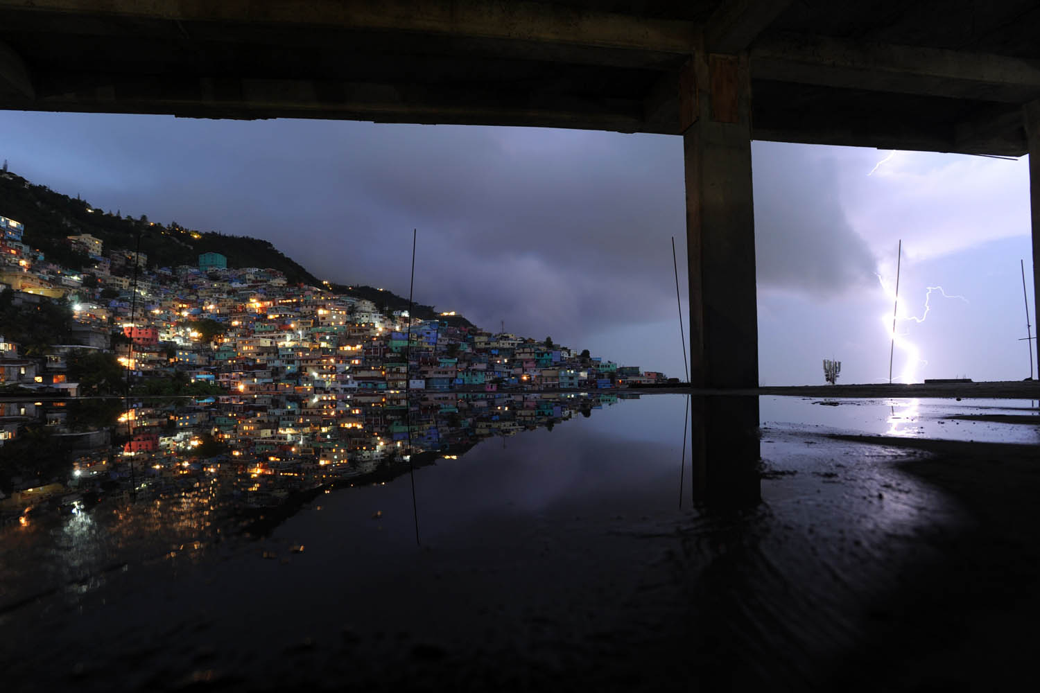 May 19, 2014. A long exposure shows lightning in the sky with reflection in the water on the floor of a building under construction during an evening thunderstorm in the Haitian capital Port-au-Prince.