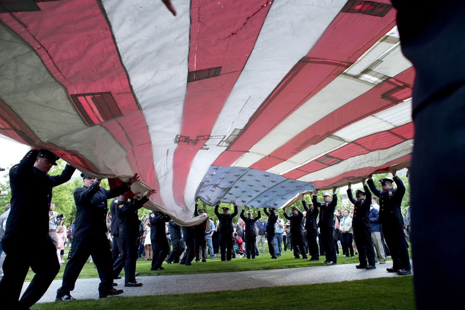 May 21, 2014. The National 9/11 Flag is furled by New York City firemen during a ceremony marking the opening  of the 9/11 Memorial Museum in New York. After the ceremony the flag was transferred into the museum's permanent collection.