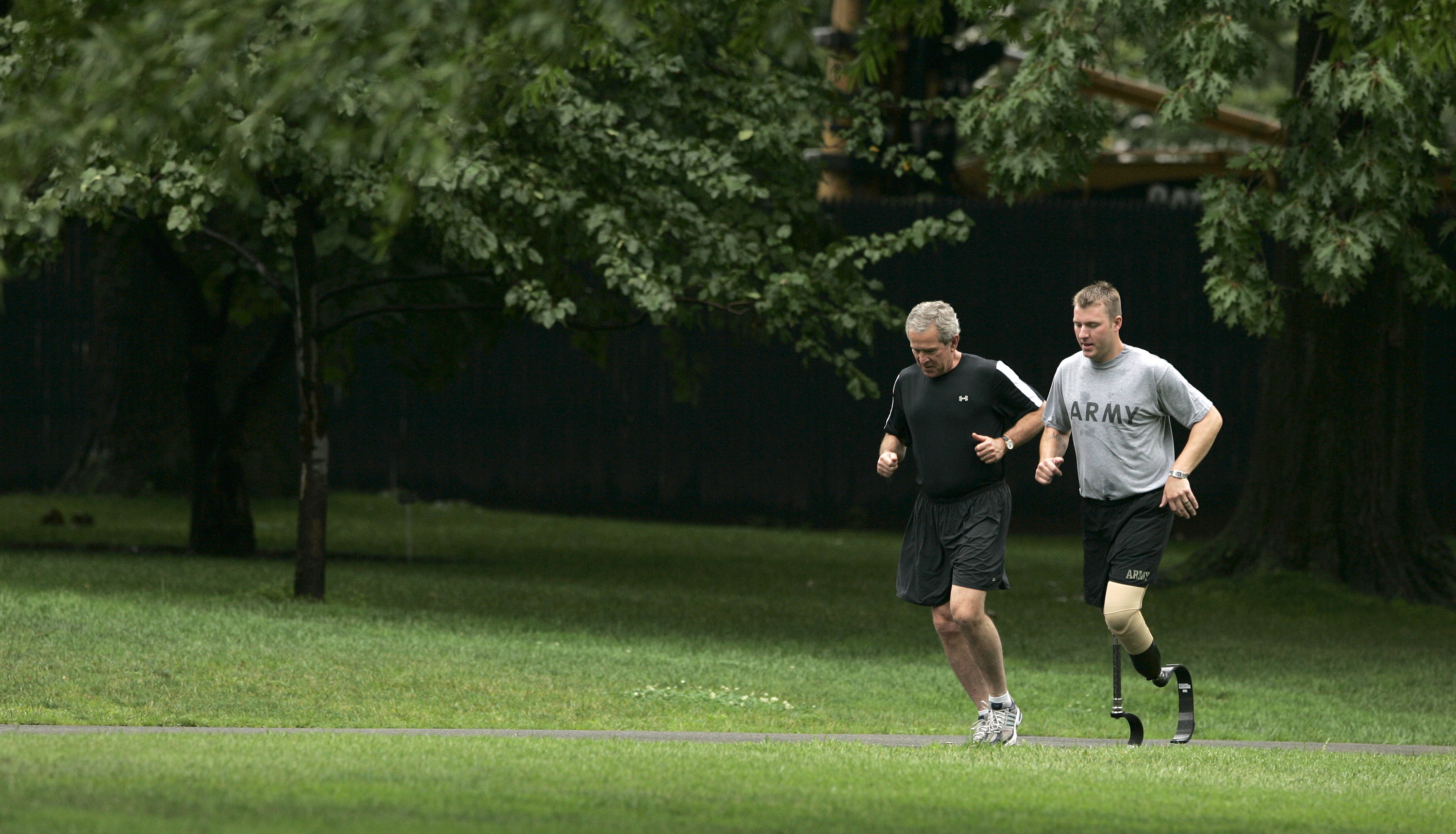 Former US President George W. Bush jogs with Army Staff Sergeant Christian Bagge, at the White House in Washington on June 27, 2006.