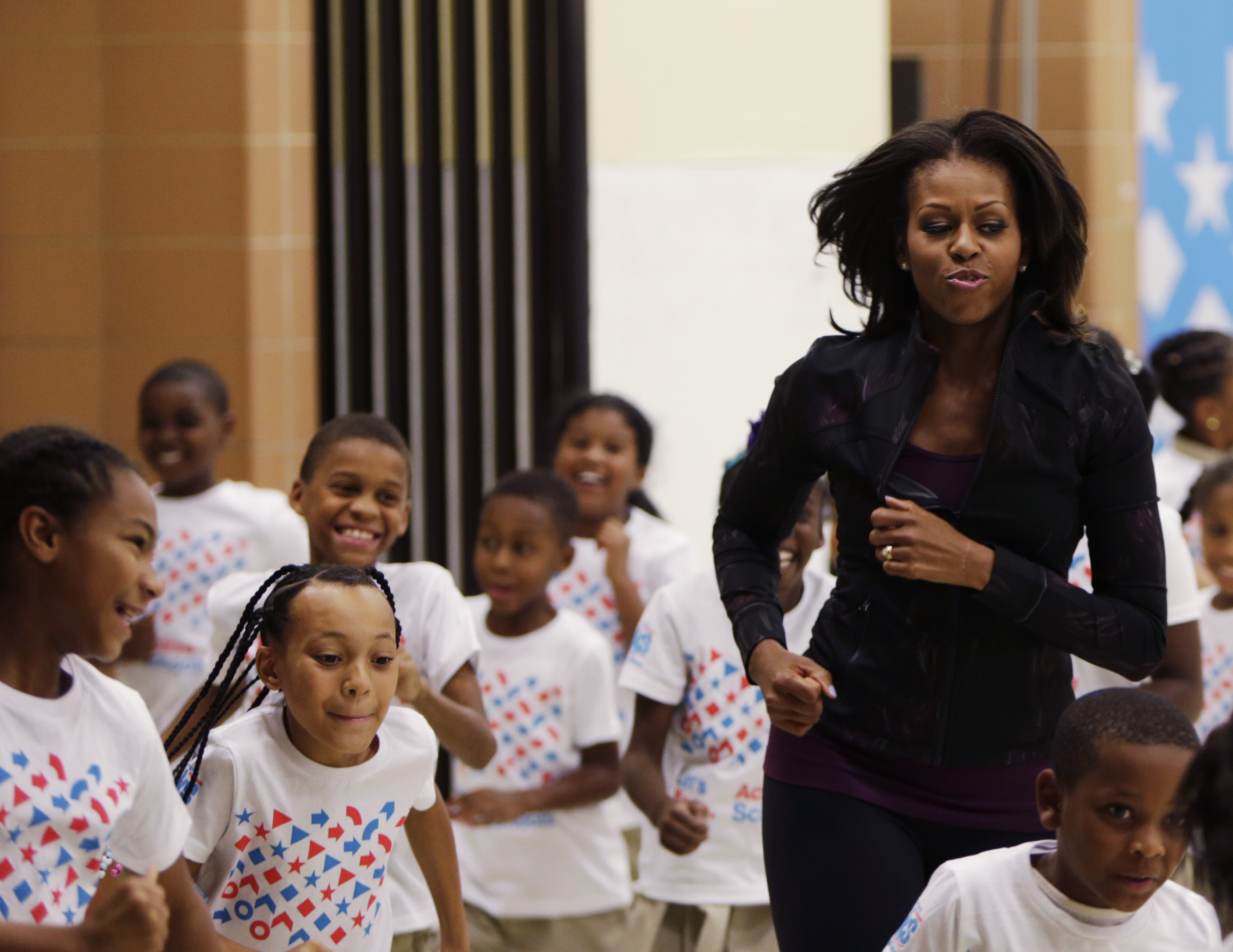 U.S. First Lady Michelle Obama jogs with children at a back-to-school event at Orr Elementary School in Washington on September 6, 2013.