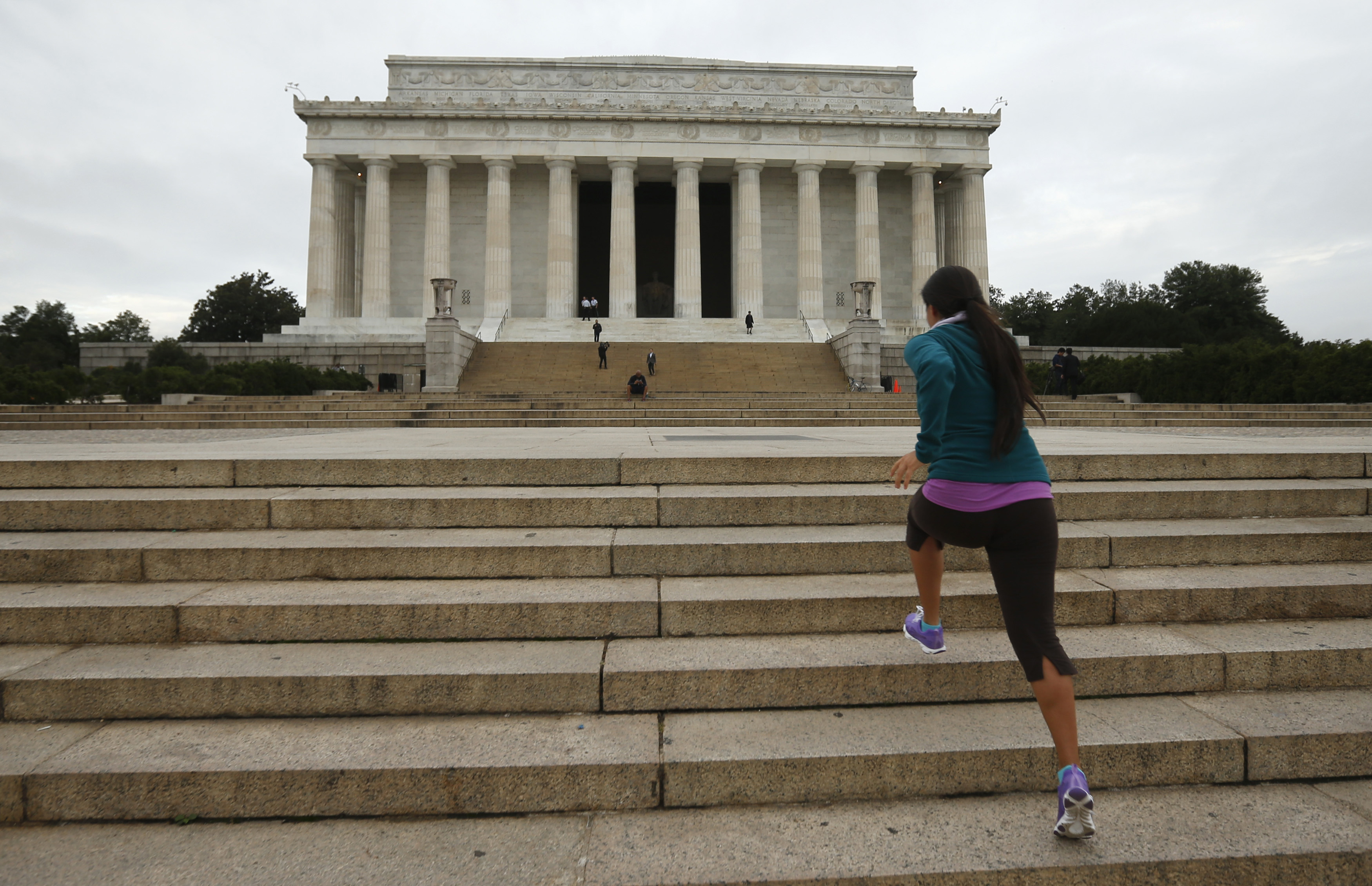 Natali Segovia, a tourist from Arizona, runs up the steps of the Lincoln Memorial as it is re-opened to the public in Washington on October 17, 2013.