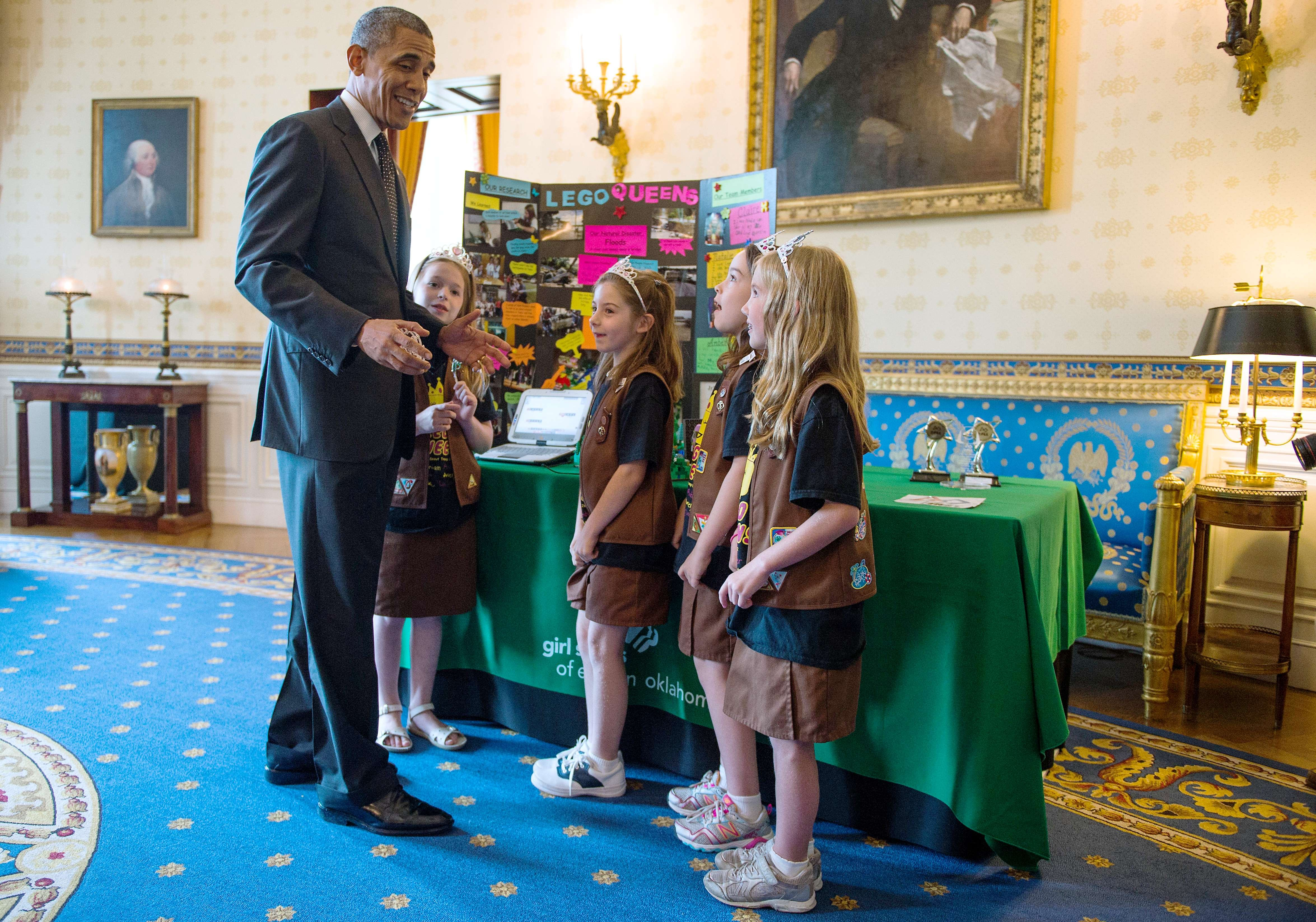 US President Barack Obama talks with a Girl Scout Brownie troop from Tulsa, Okla. about their design for a  flood proof  bridge, during the White House Science Fair in Washington on May 27, 2014.