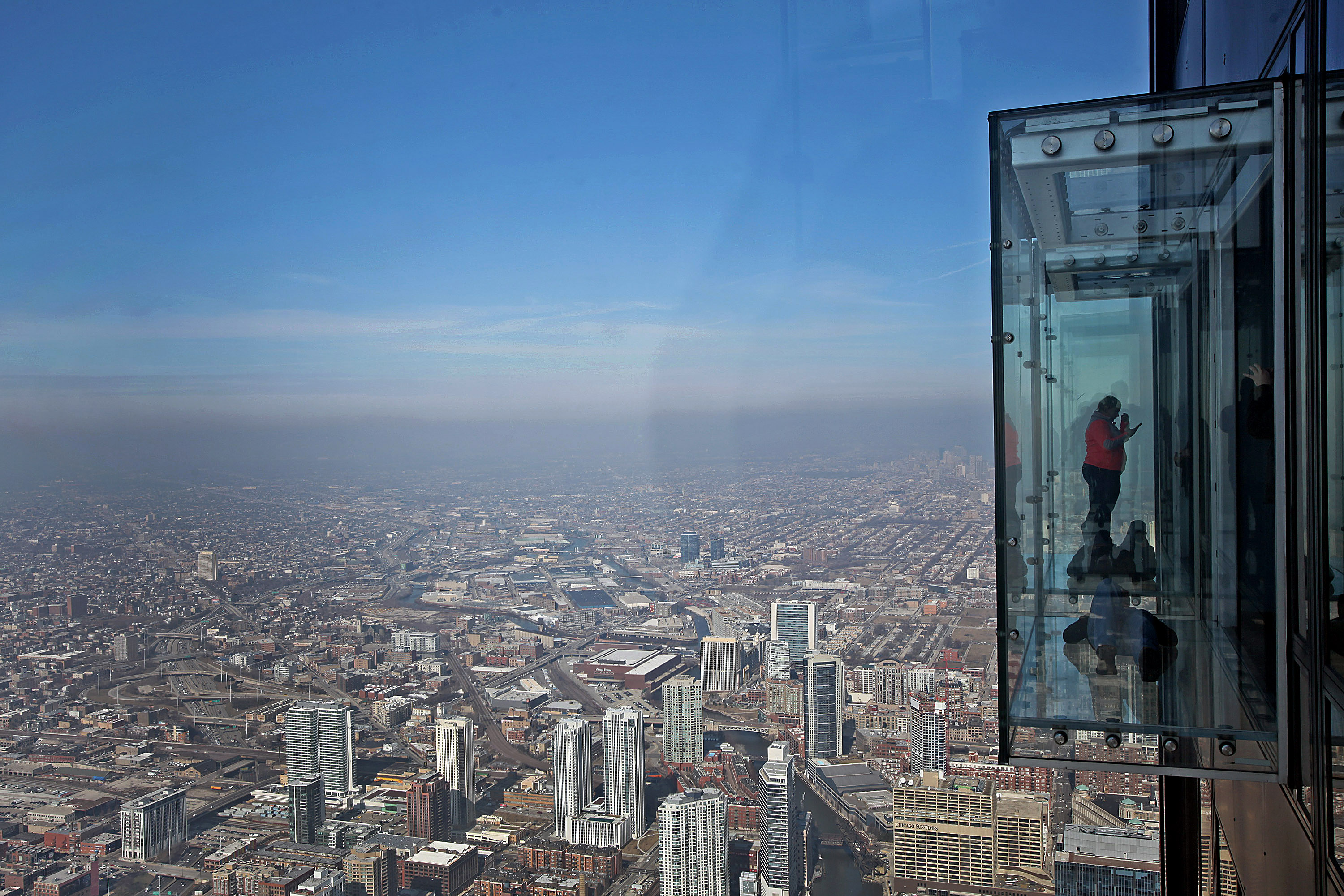 Visitors stand on the glass balcony at the skydeck of the Willis Tower in Chicago, Illinois, U.S., on Wednesday, Feb. 13, 2013.