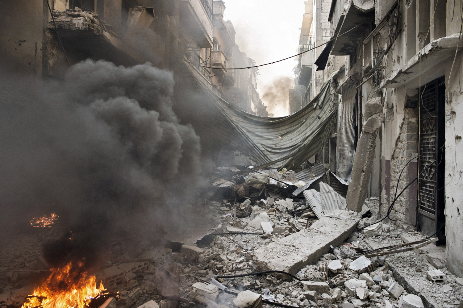 A street in the Qabaris neighborhood of Homs lies in ruins. Government soldiers use small fires to melt the plastic from cables and wires stripped from destroyed buildings. They say it is to prevent the wires from being used for improvised explosive devices, but the copper within can also be sold for cash.  May 12, 2014.