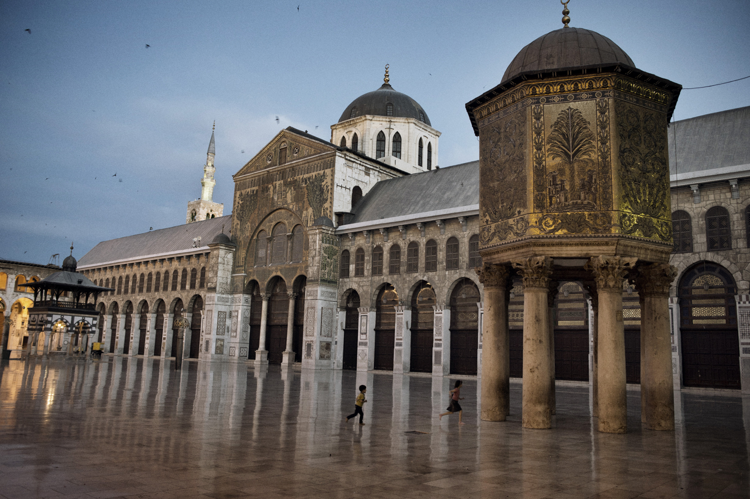 Two children run in the courtyard of the Umayyad Mosque in Damascus. May 18, 2014.