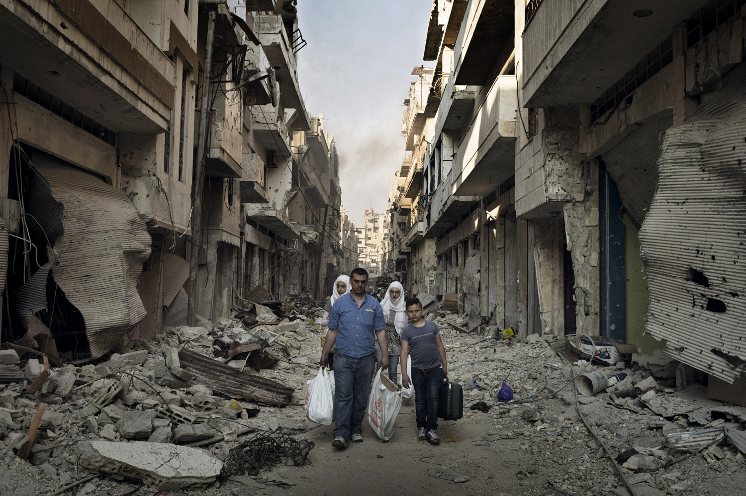 Residents walk down a street after collecting their belongings in the Qabaris neighborhood of the Old City of Homs. May 12, 2014.