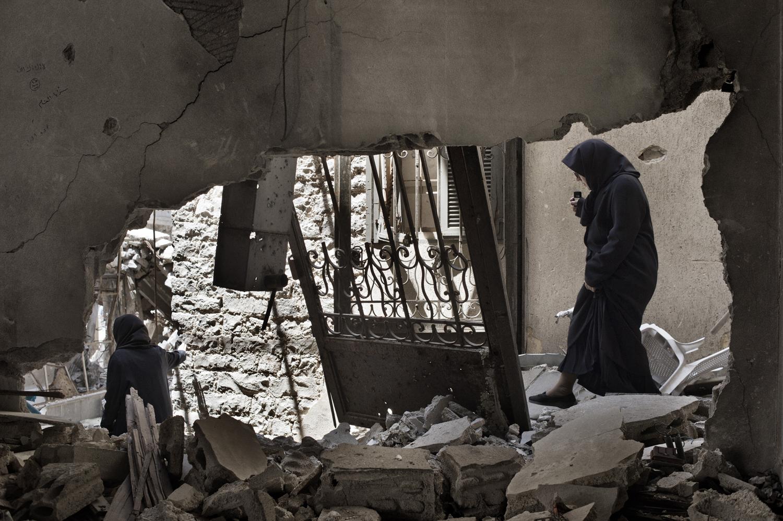 Women walk through a destroyed building in the Khaldiyeh neighborhood of Homs. May 13, 2014.