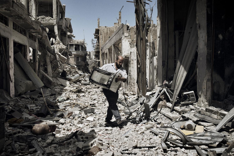 A man carefully walks down a destroyed street  in the Khaldiyeh neighborhood of Homs. May 13, 2014.