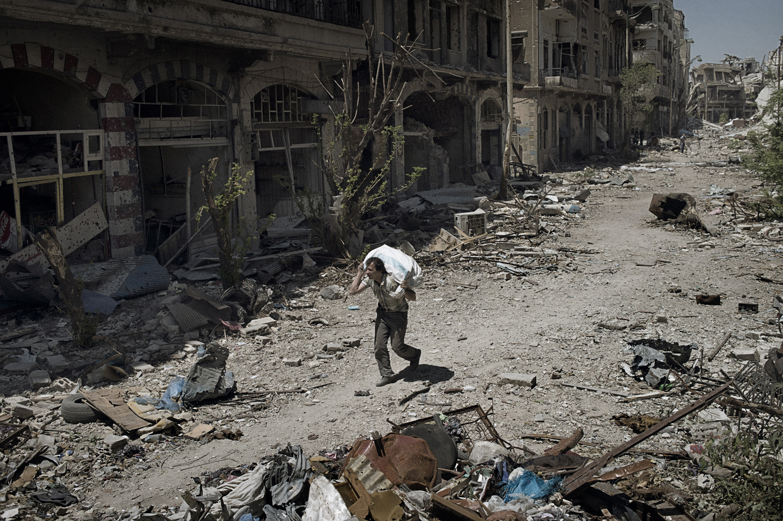 A man walks down a destroyed street with salvaged belongings in the Khaldiyeh neighborhood of Homs. May 13, 2014.