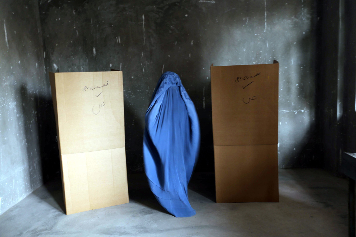 Jun. 14, 2014. A burqa-clad Afghan woman casts her ballot at a polling station during Presidential elections run-off, in Herat, Afghanistan.