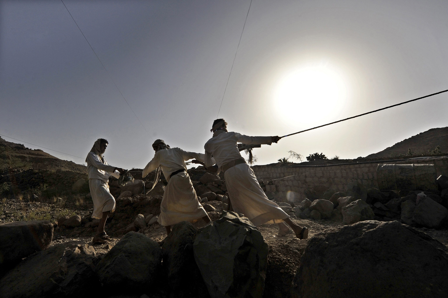 Jun. 18, 2014. Yemeni farmers pull ropes as they dig a wall in search of water due to a fuel shortage for months on the outskirts of Sana'a, Yemen.