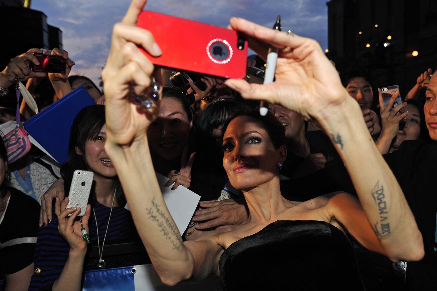 Jun. 23, 2014. US actress and cast member Angelina Jolie (C) takes a selfie with a fan as she attends the premiere of 'Maleficent' in Tokyo, Japan.