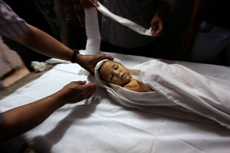 Jun. 25, 2014. The body of three-years old Joad Al-Danaf is prepared at the Al Shifa hospital morgue in the central Gaza City.