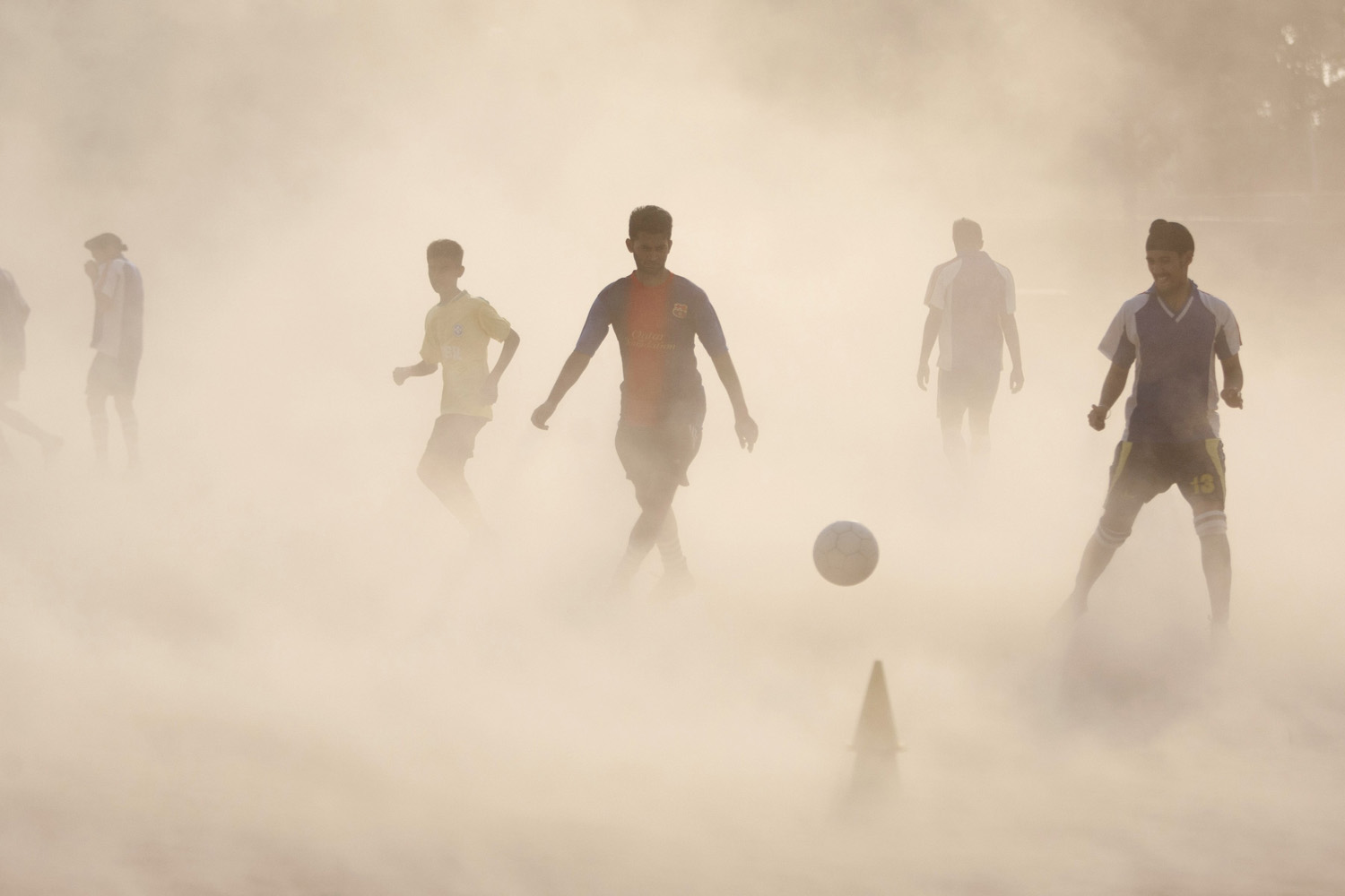 Jun. 11, 2014. Aspiring young Indian soccer players continue with their practice during a dust storm in Jammu, India. Soccer fans around the world are gearing up to watch the Soccer World Cup that begins in Brazil Thursday.