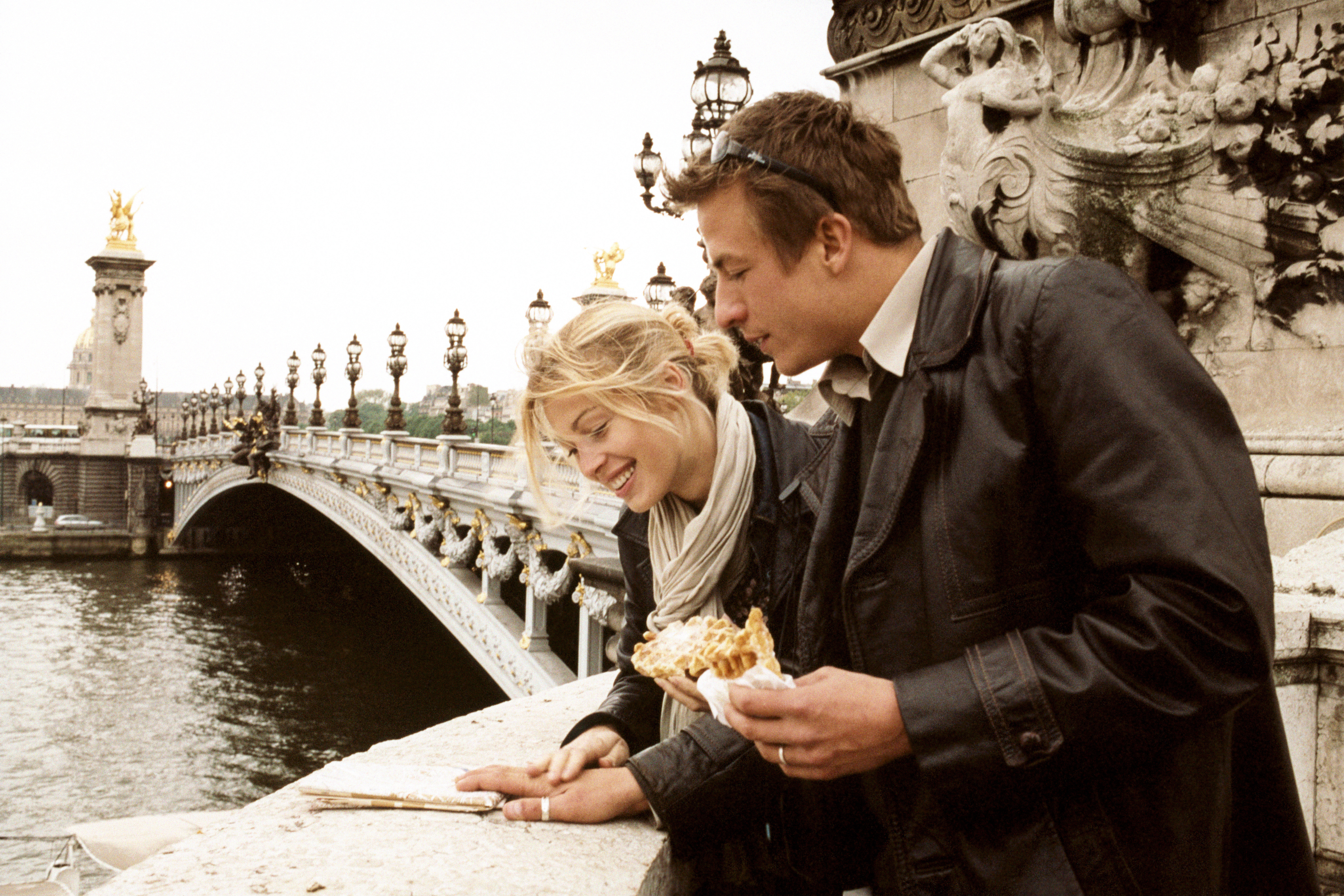 Young couple looking at map on Alexandre III bridge in Paris, France.