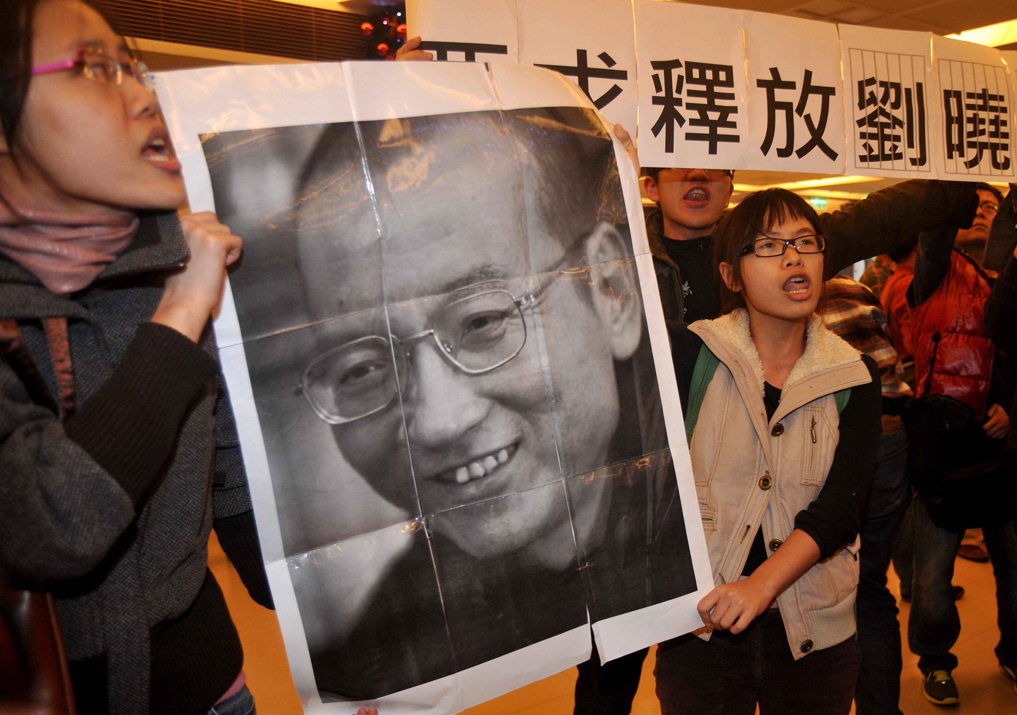 Demonstrators hold a portrait of China's detained Nobel Peace Prize winner Liu Xiaobo demanding his immediate release during a protest in the lobby of Taipei's National Palace Museum where China's top negotiator Chen Yunlin visited on Dec. 20, 2010.