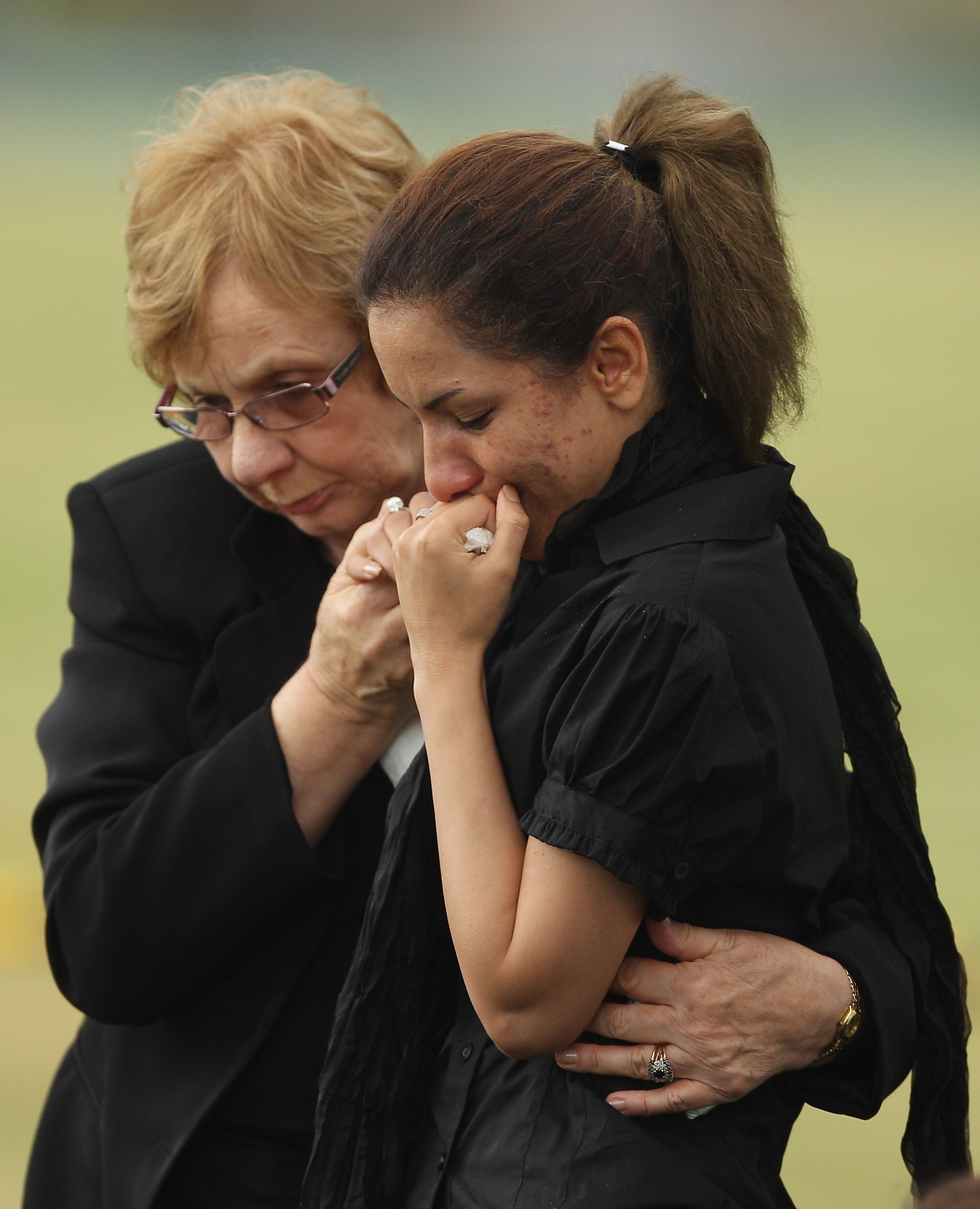 A mourner is comforted at a Christian funeral service for the victims of the Christmas Island asylum-seeker shipwreck at Castlebrook Memorial Park on Feb. 15, 2011, in Sydney.