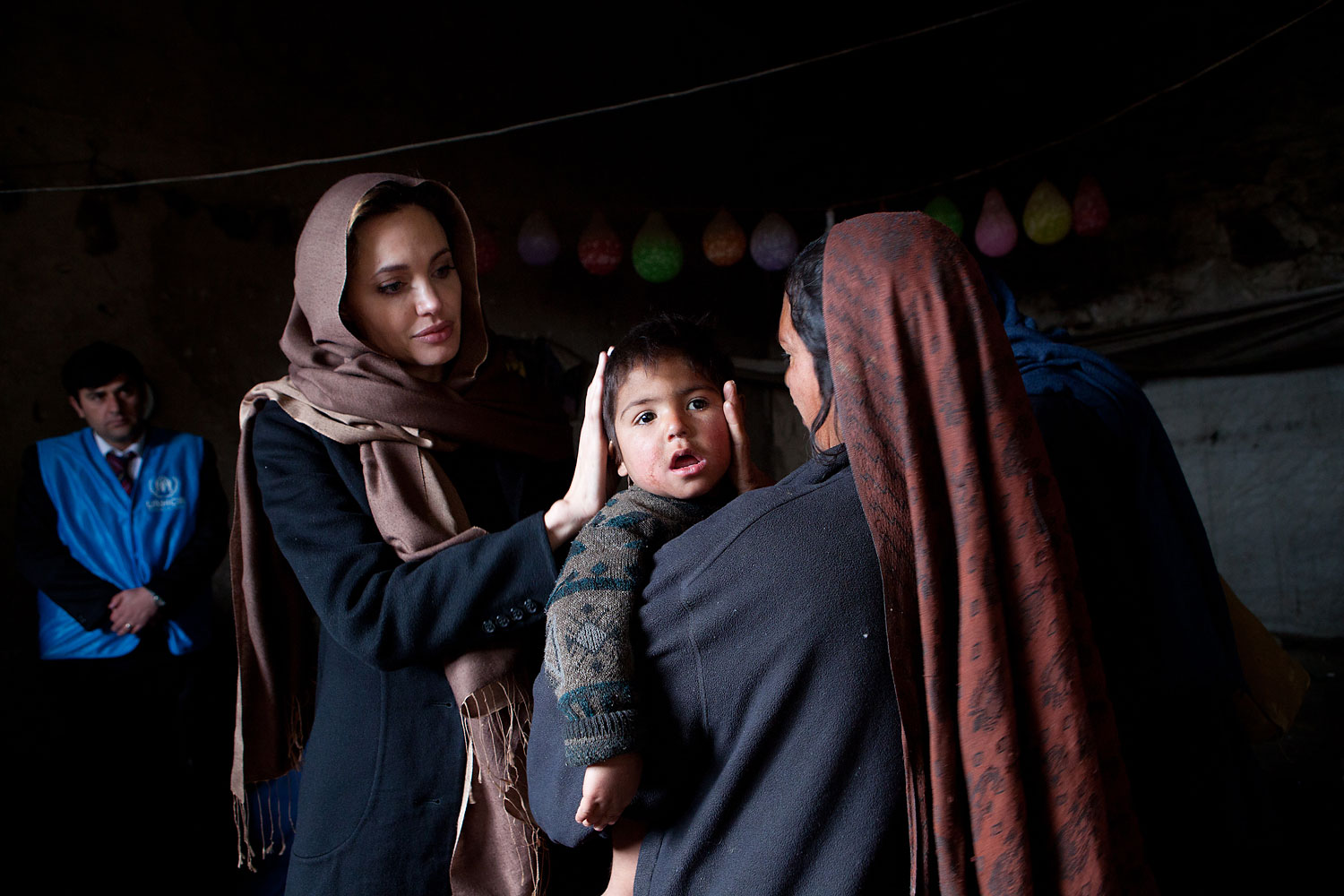 Angelina Jolie, meets with Khanum Gul, 35, a mother of 8 and her youngest son, Samir at their makeshift home at Tamil Mill Bus site in Kabul city, Afghanistan in Feb. 2011.