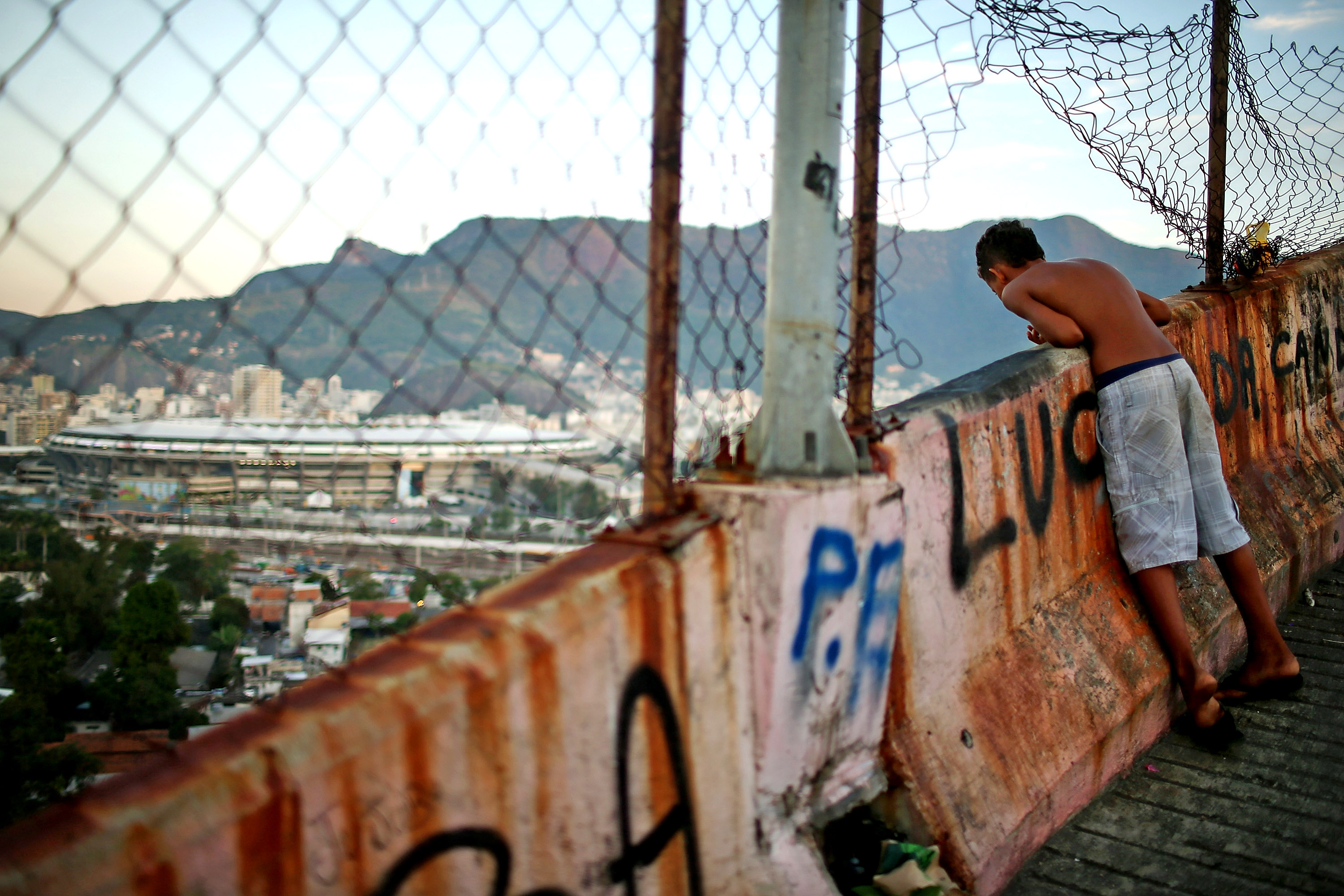 A boy looks out for a fallen kite as kids fly kites in the Mangueira favela which overlooks famed Maracana Stadium on June 5, 2014 in Rio de Janeiro.