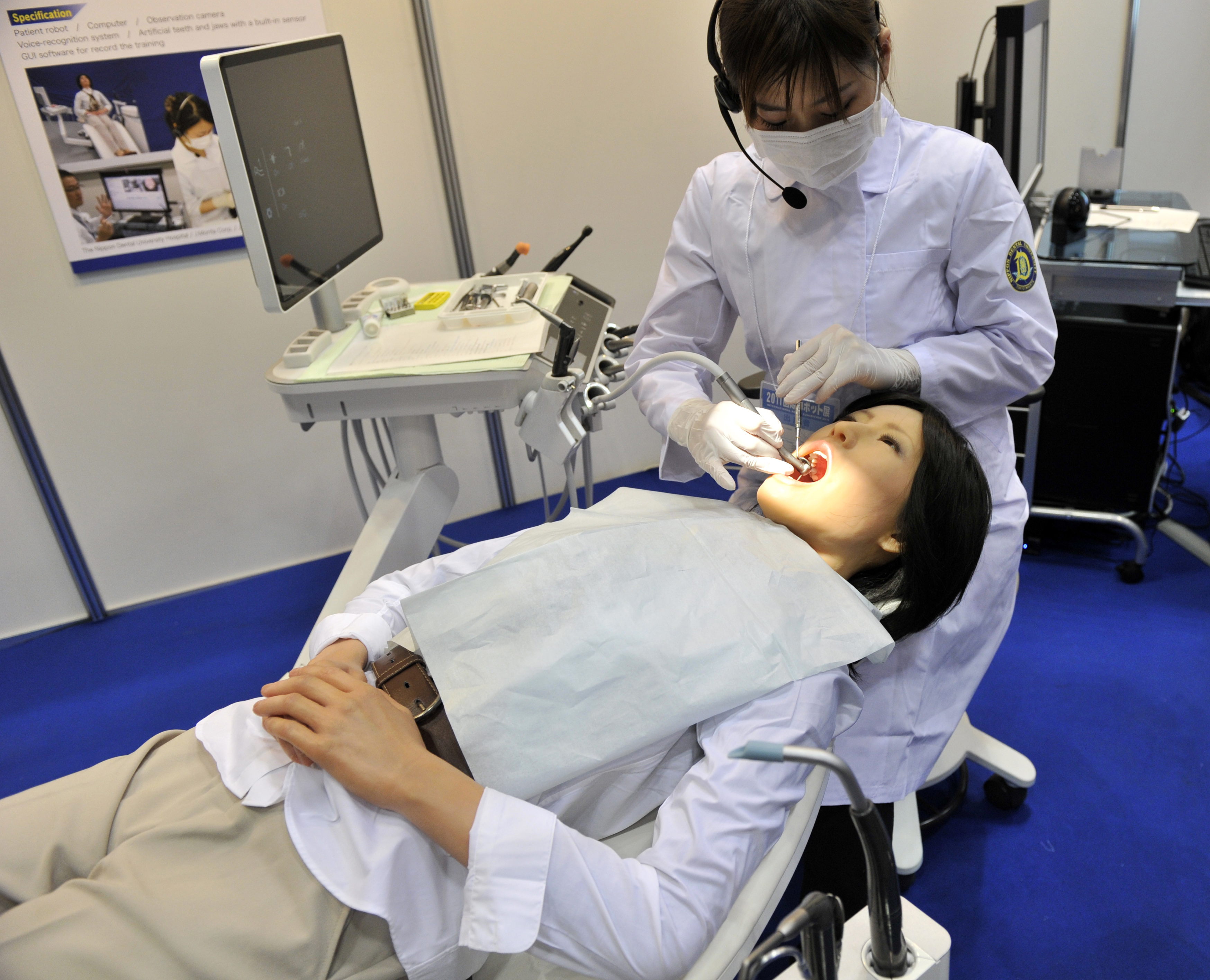 "A Nippon Dental University Hospital staff member demonstrates a humanoid robot dental therapy simulator named ""Simroid"" at the International Robot Exhibition in Tokyo on November 9, 2011."