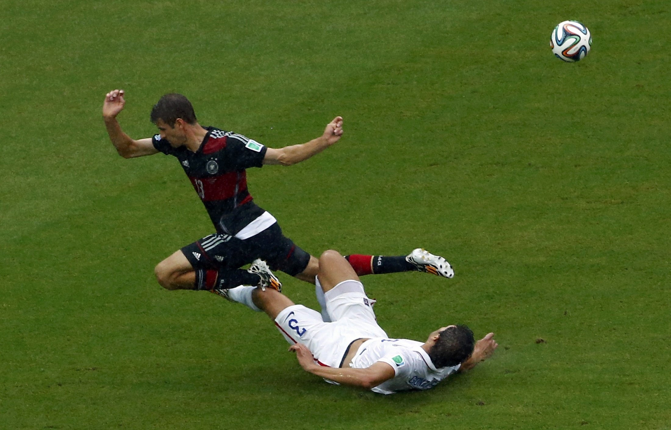 Germany's Thomas Mueller falls over Omar Gonzalez of the U.S. during their 2014 World Cup Group G soccer match at the Pernambuco arena in Recife, Brazil on June 26, 2014.