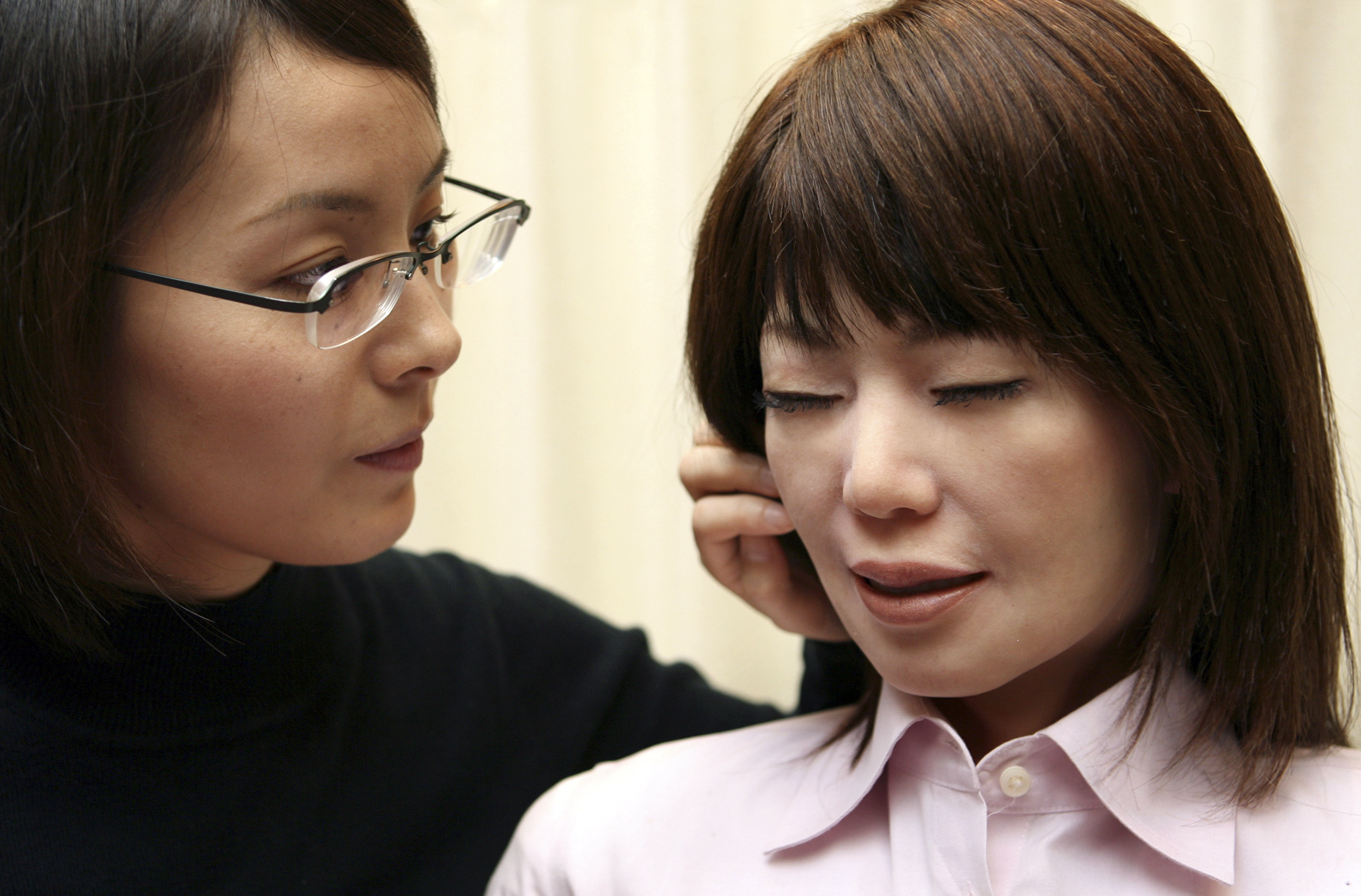Andoroid Repliee Q2 (R) reacts as graduate student Motoko Noma touches her face at an exhibition during Core Technology Symposium in Tokyo on October 31, 2006.