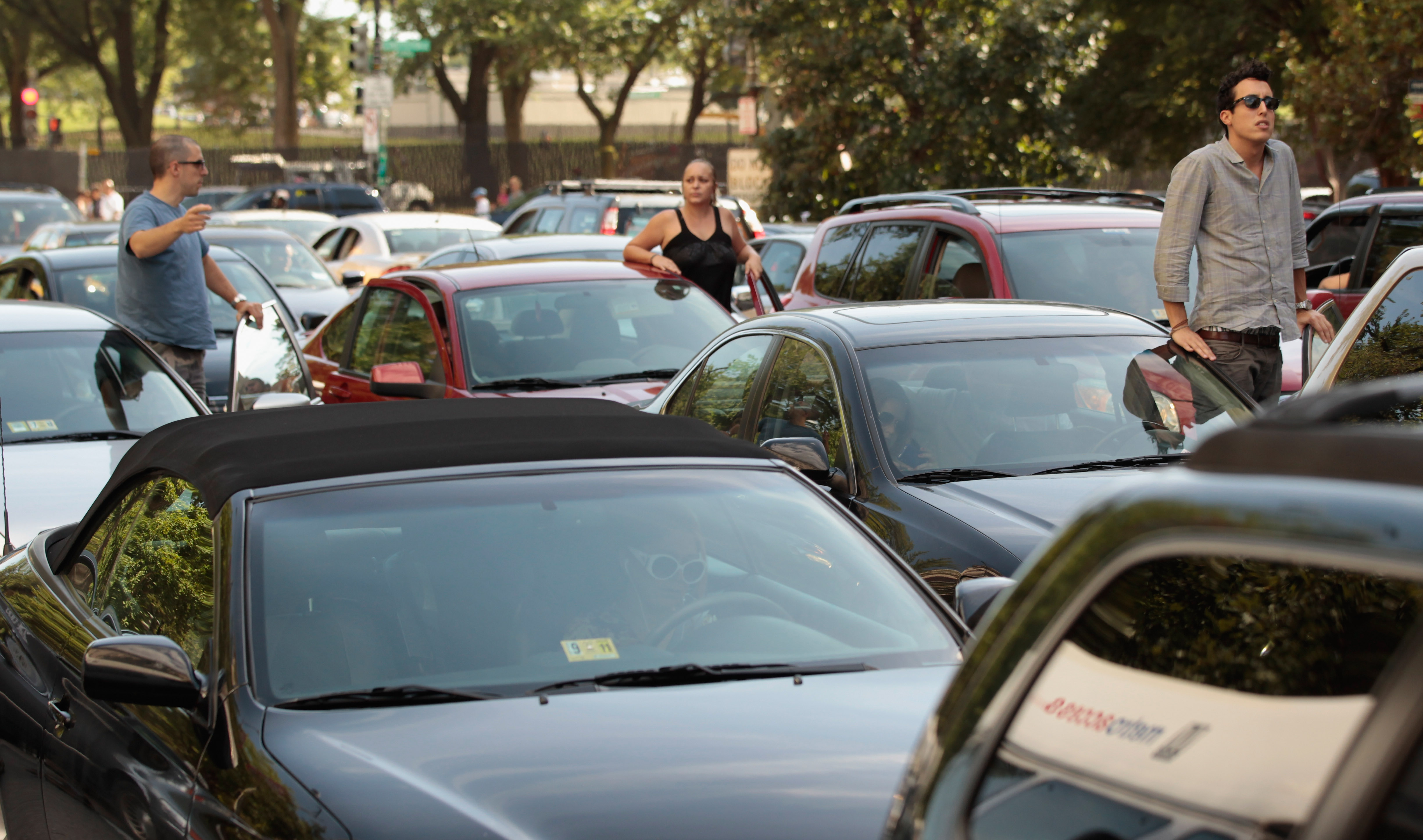 Drivers climb out of their cars to survey a traffic jam on August 23, 2011 in Washington D.C.