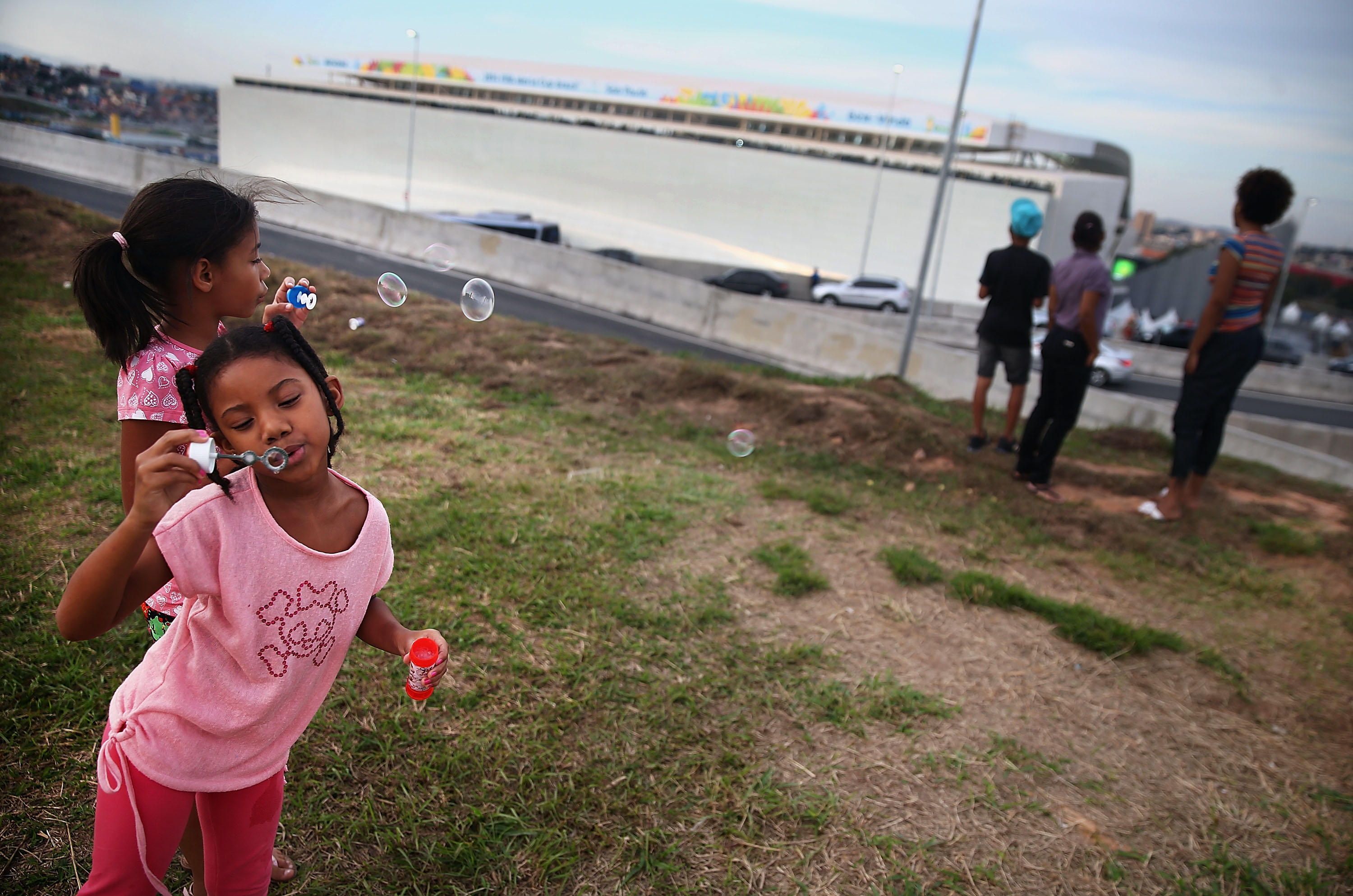 Residents from a nearby community gather while catching a glimpse outside Itaquerao stadium, also known as Arena de Sao Paulo and Arena Corinthians, on June 8, 2014 in Sao Paulo.