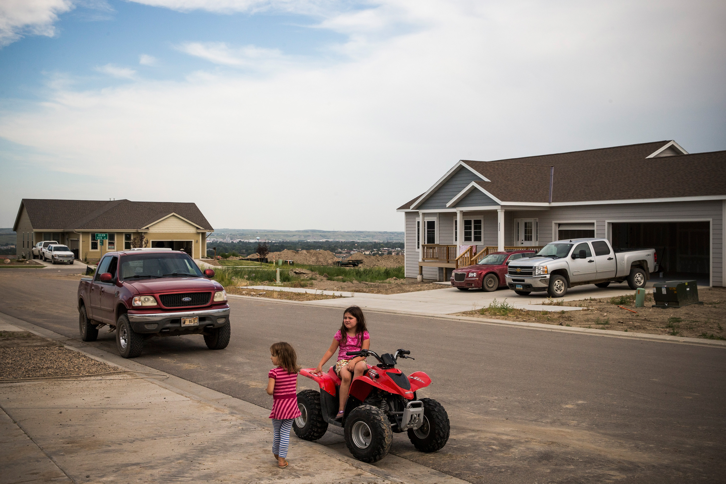 Two girls play on a four-wheeler in a new subdivision on July 24, 2013 in Williston.