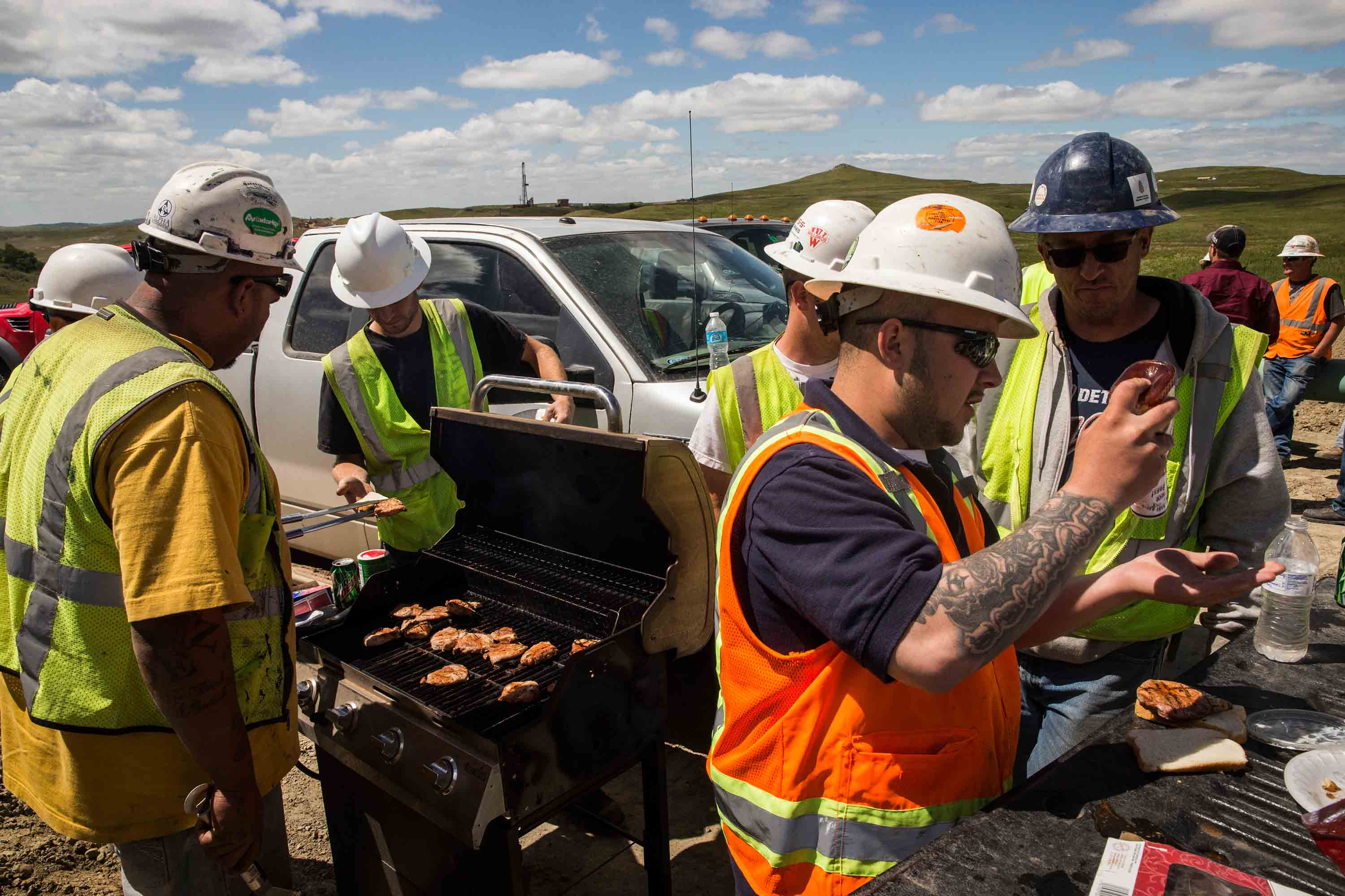 Construction workers specializing in pipe-laying grill lunch while working on a pipeline that will stream line oil production from drill sites to train yards and oil refineries on July 25, 2013 outside Watford City.